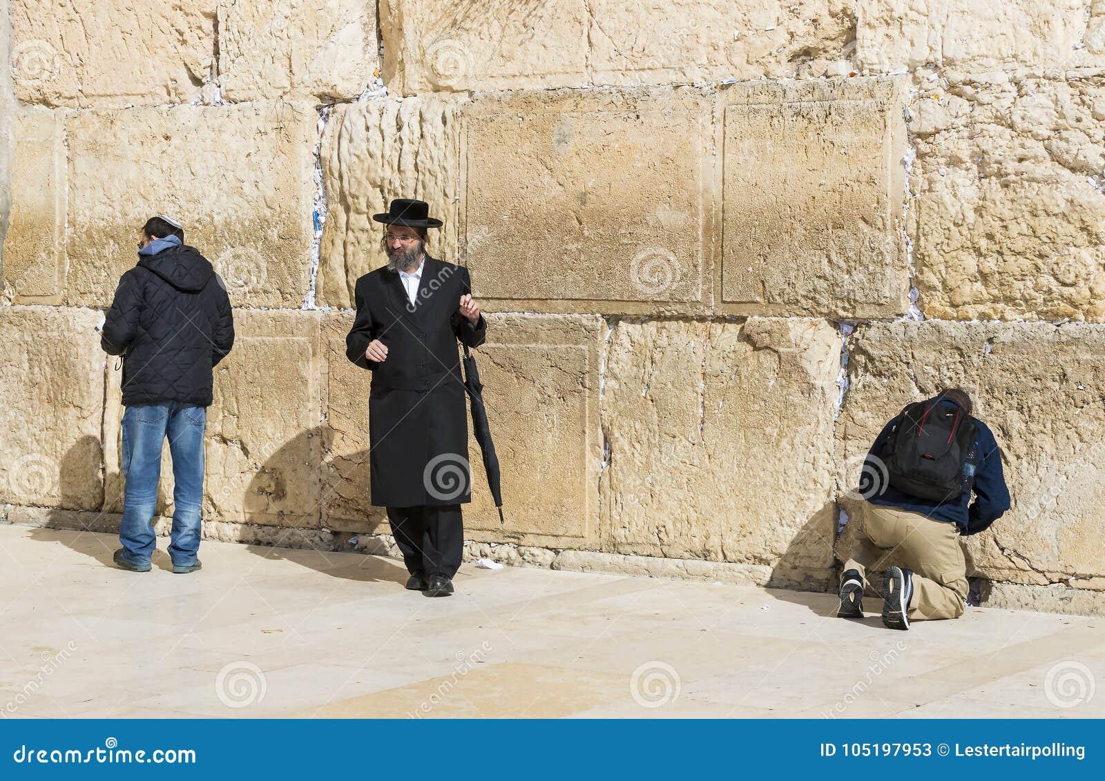 Pilgrims ber på väggen av gråta av det heliga stället av det judiska folket och mitten av dyrkan av kristen runt om