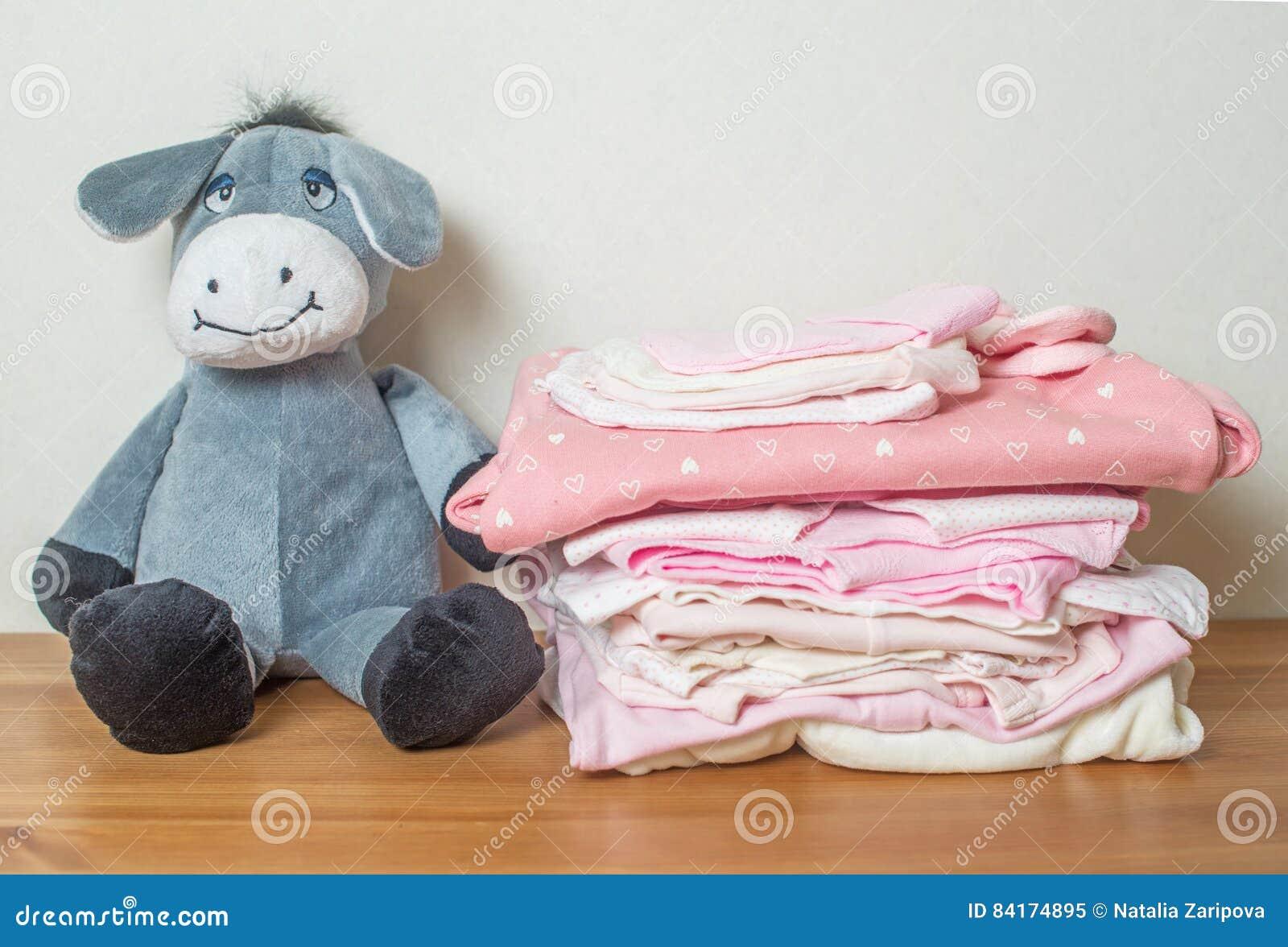 Pilha da roupa para a menina recém-nascida no fundo de madeira com brinquedo