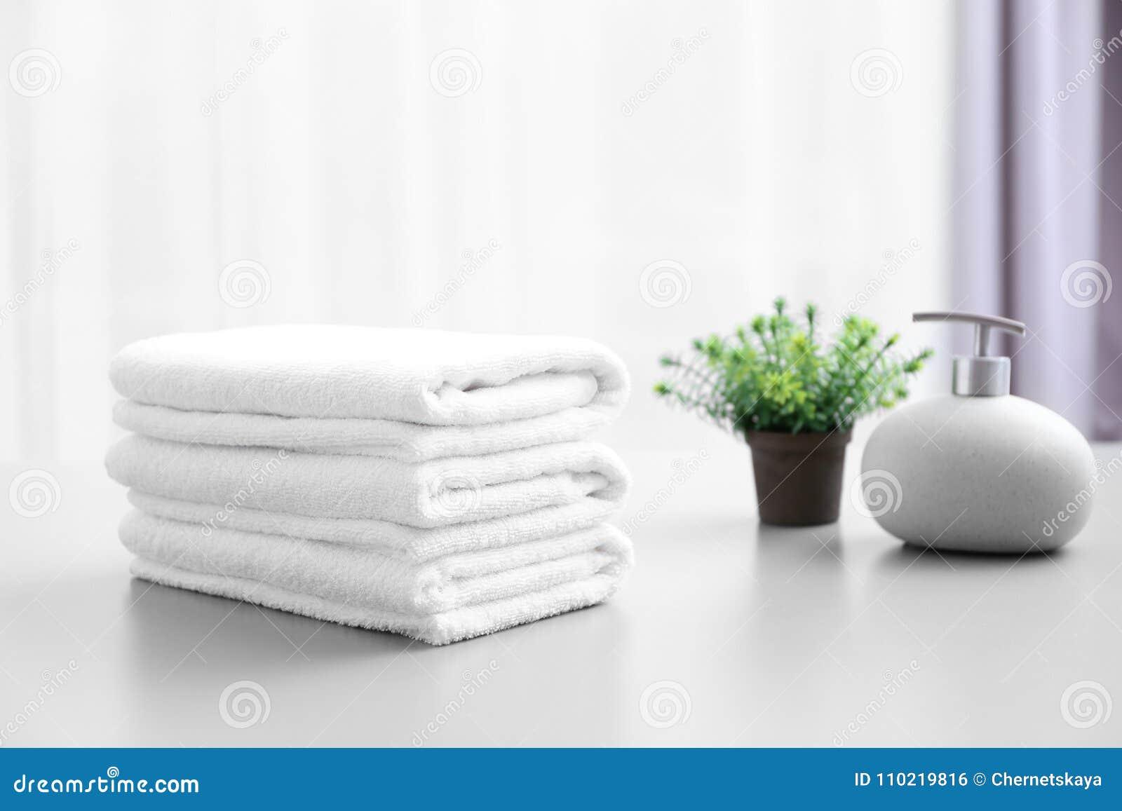 Pilha das toalhas limpas brancas na tabela