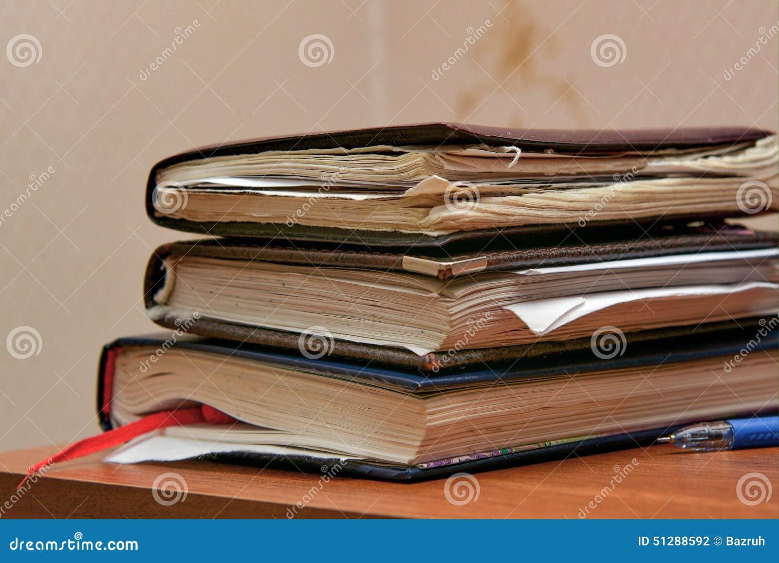 Pilha de cadernos velhos do estudante na tabela