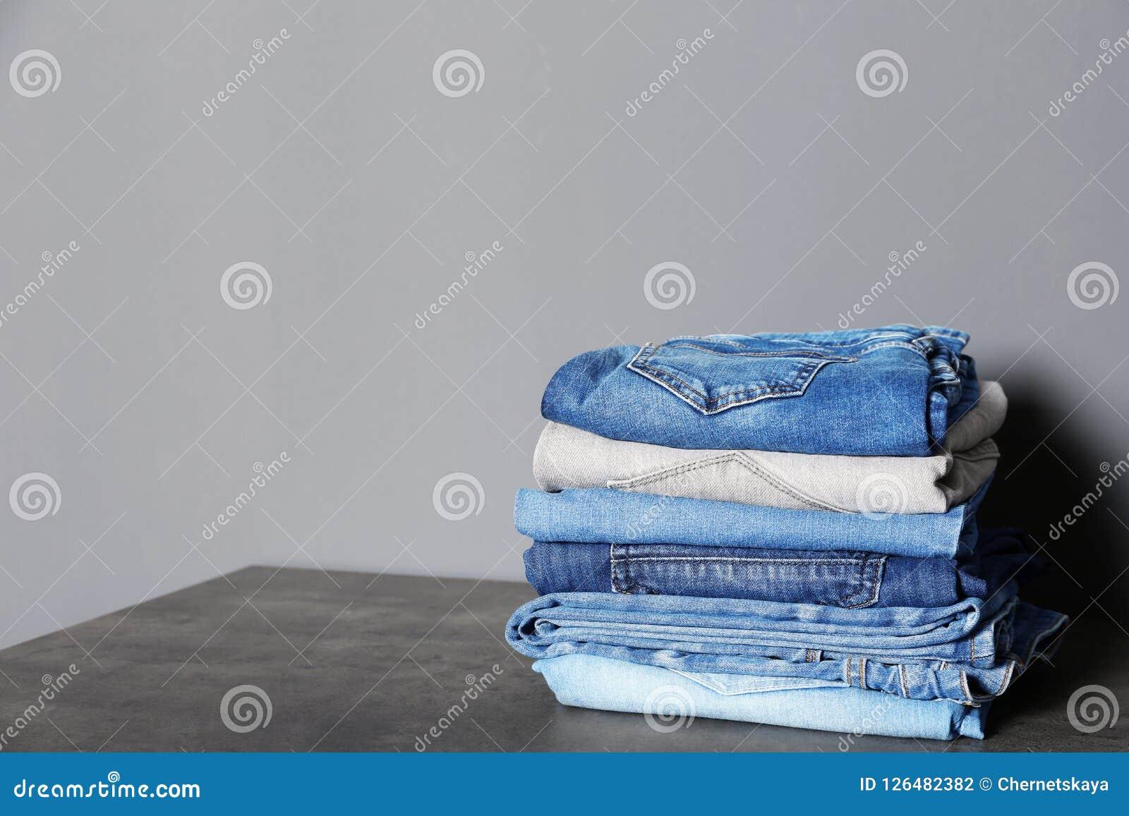 Pilha de calças de brim diferentes na tabela contra o fundo cinzento Fotografia de Stock