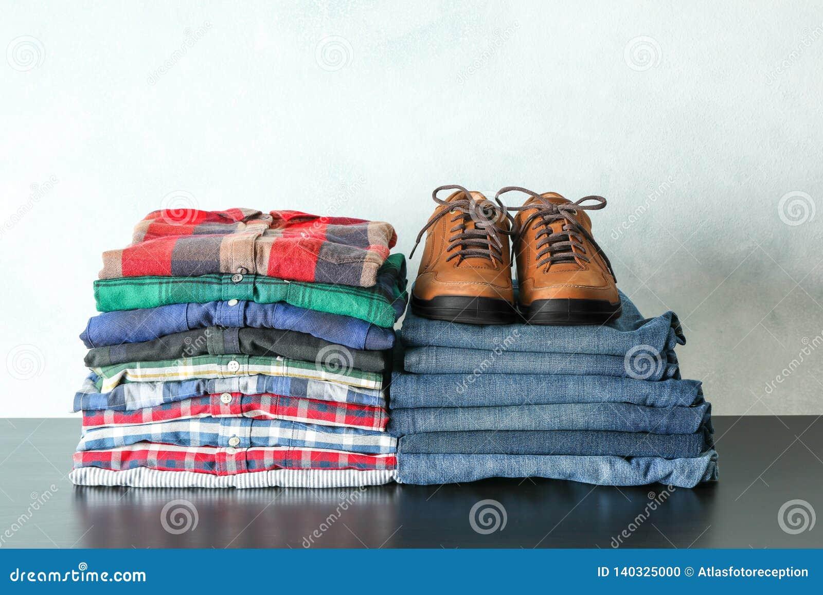 Pilha de camisas, de calças de brim e de sapatas coloridas na tabela contra o fundo claro
