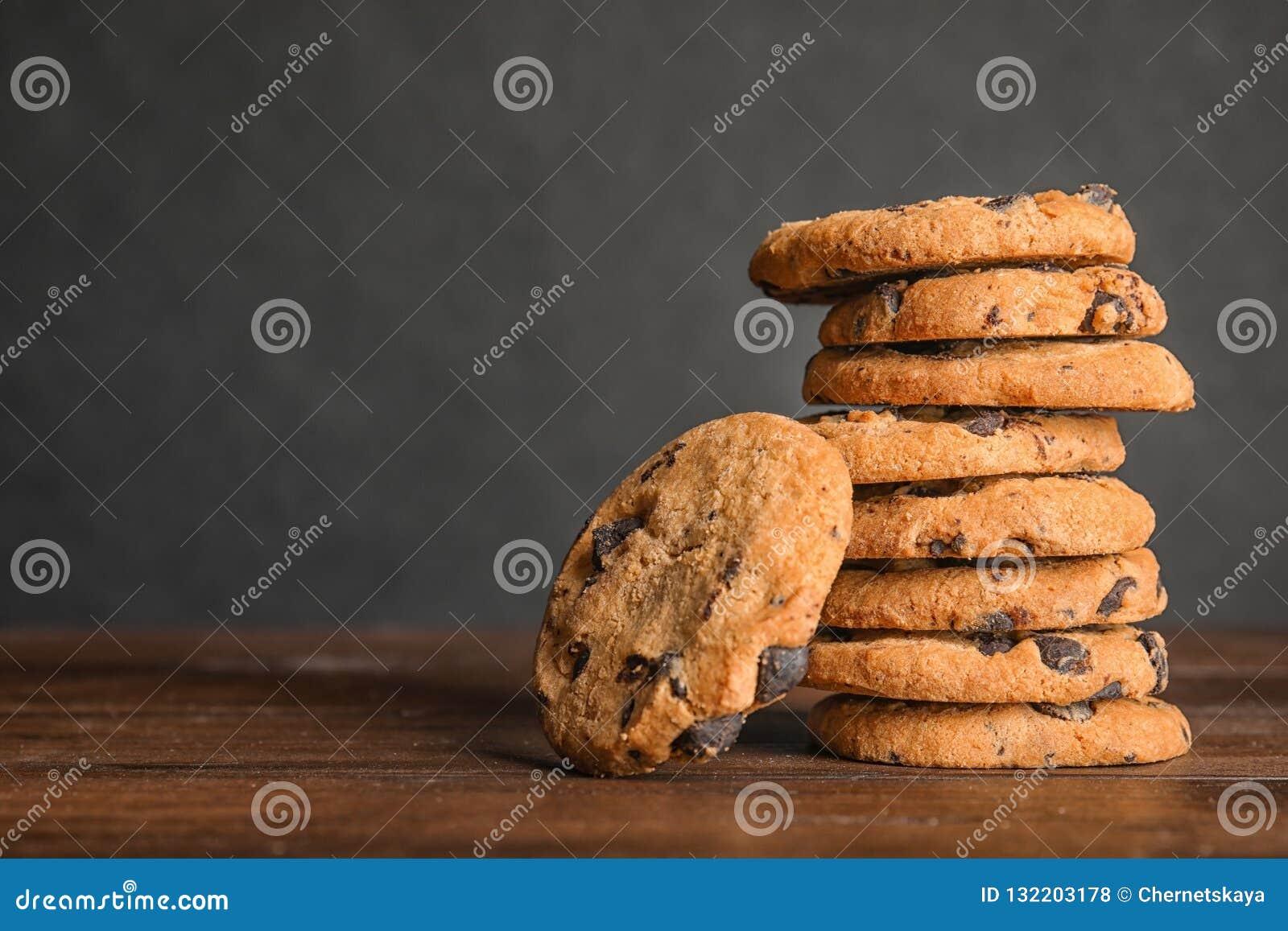 Pilha de cookies saborosos dos pedaços de chocolate na tabela de madeira