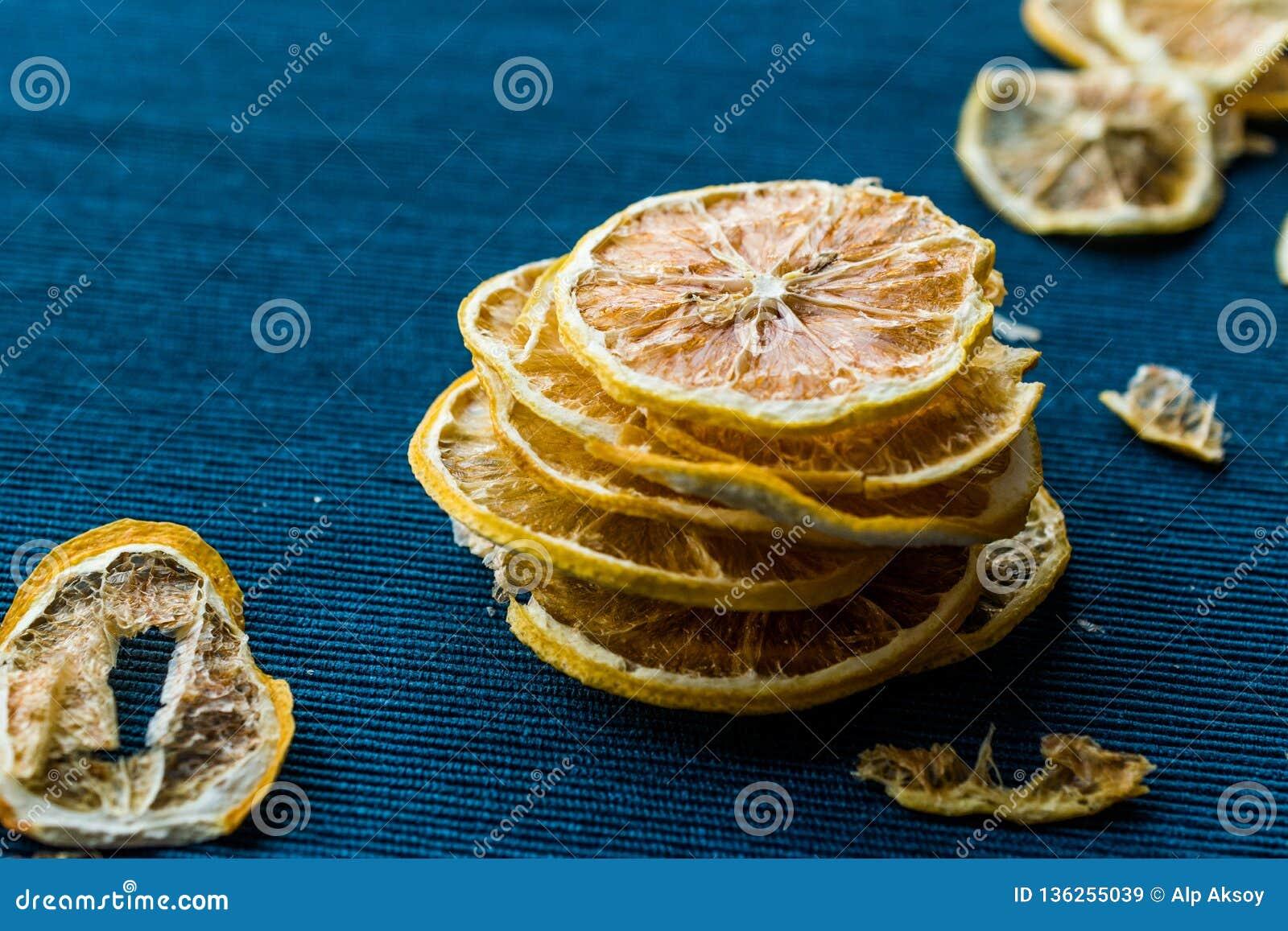 Pilha de fatias secadas do limão na superfície azul/seco e cortado