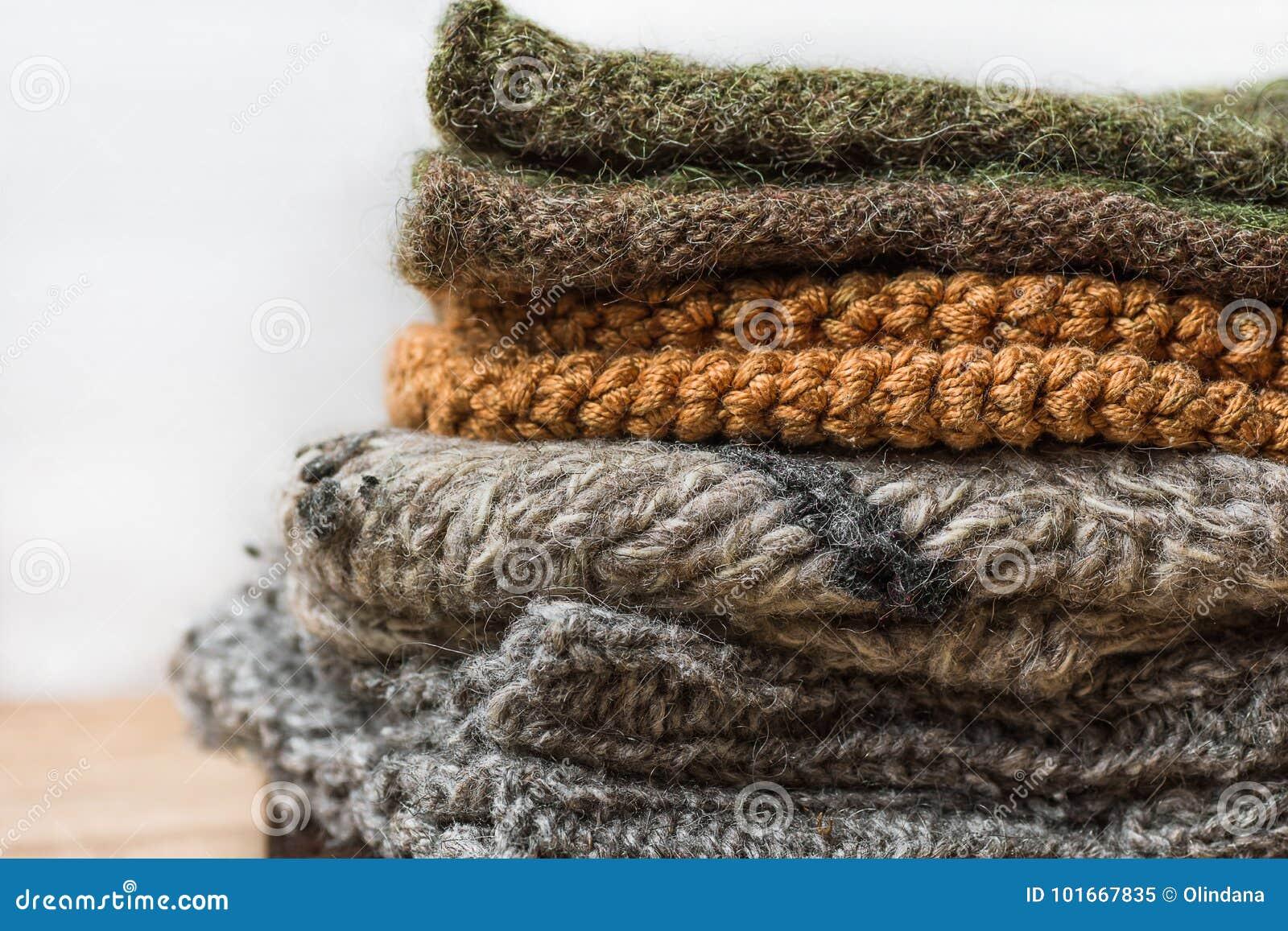 A pilha de feito a mão aquece mitenes feitos malha dos lenços das peúgas do cinza bege áspero de Brown do fio de lãs na tabela de
