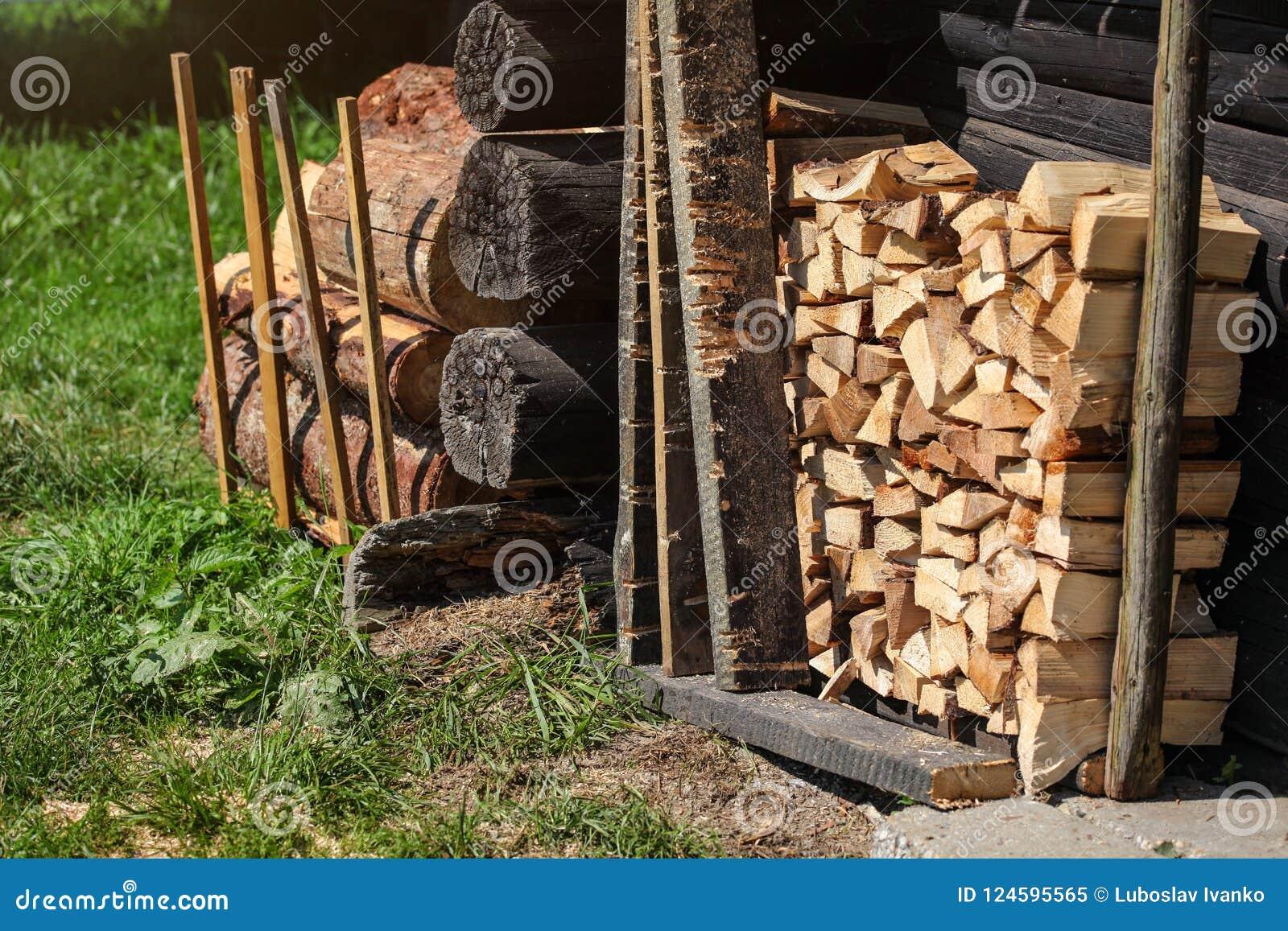 A pilha de lenha ao lado da parede de madeira velha da casa de campo, sol iluminou a grama