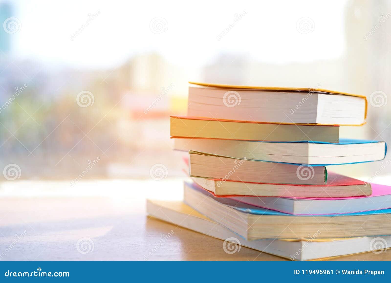 Pilha de livro na sala da biblioteca para de volta à escola e na educação no dia ensolarado perto da janela na biblioteca