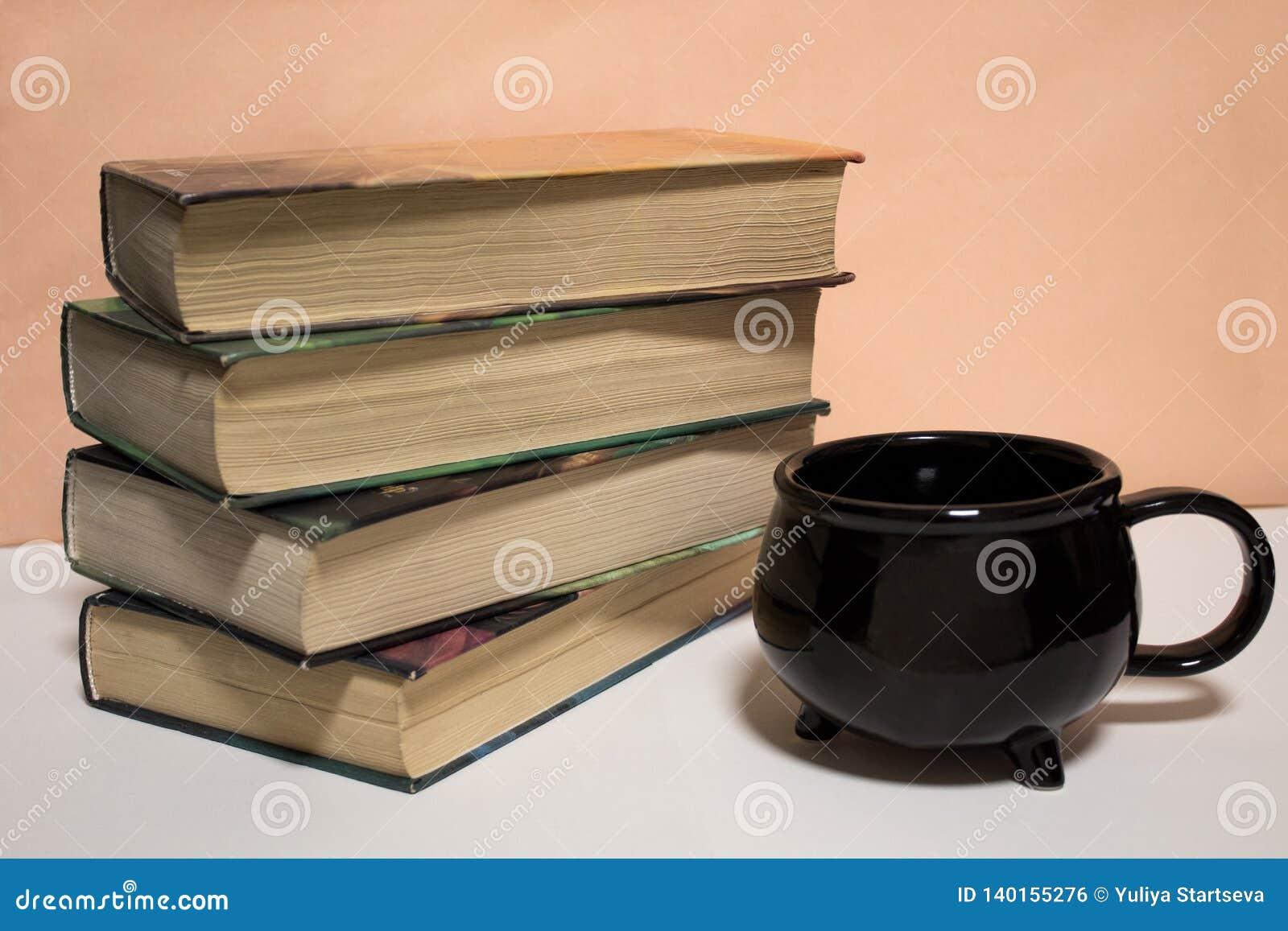 Pilha de livros e de um copo no fundo branco