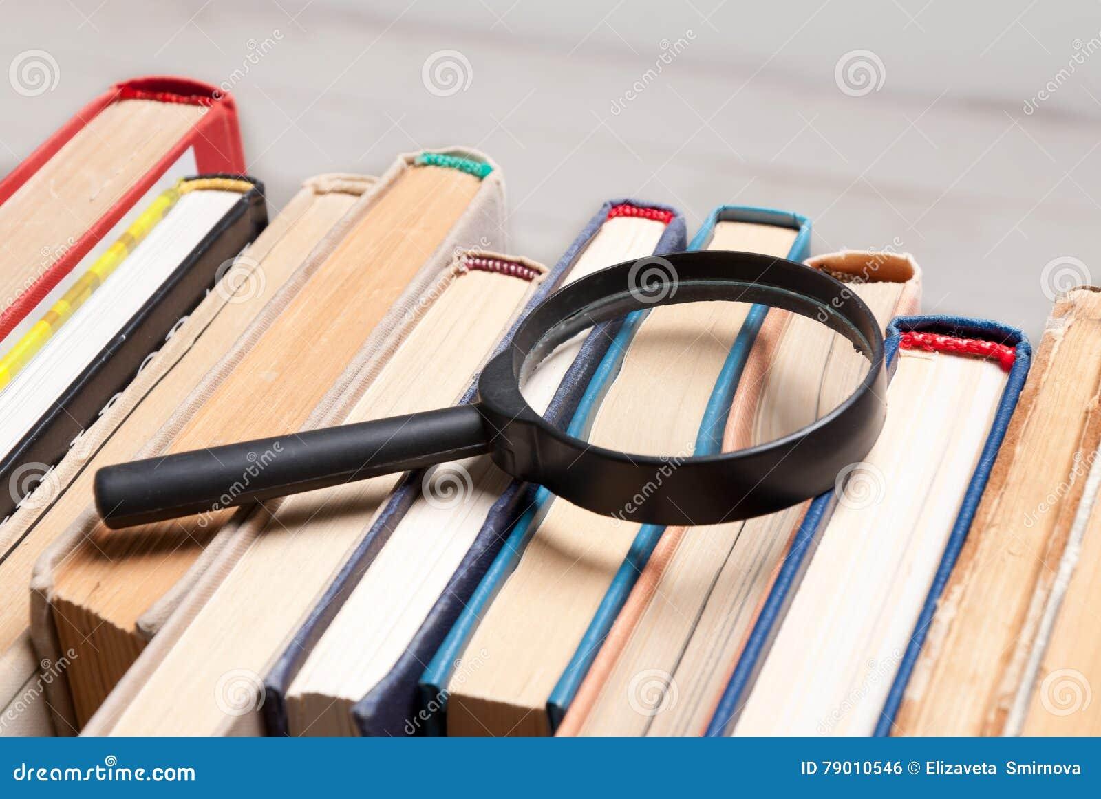 Pilha de livros velhos do livro encadernado com lupa Procure pela informação relevante e necessária em um grande número duri das