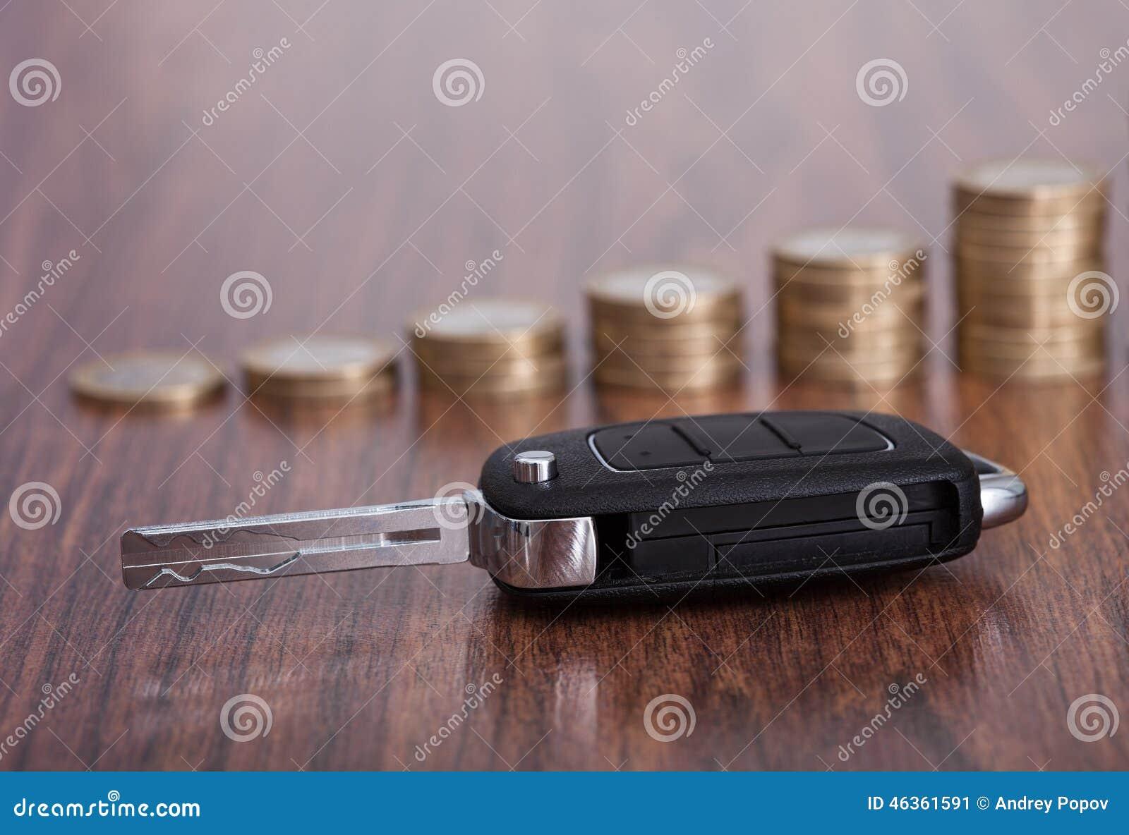 Pilha de moedas com chave do carro