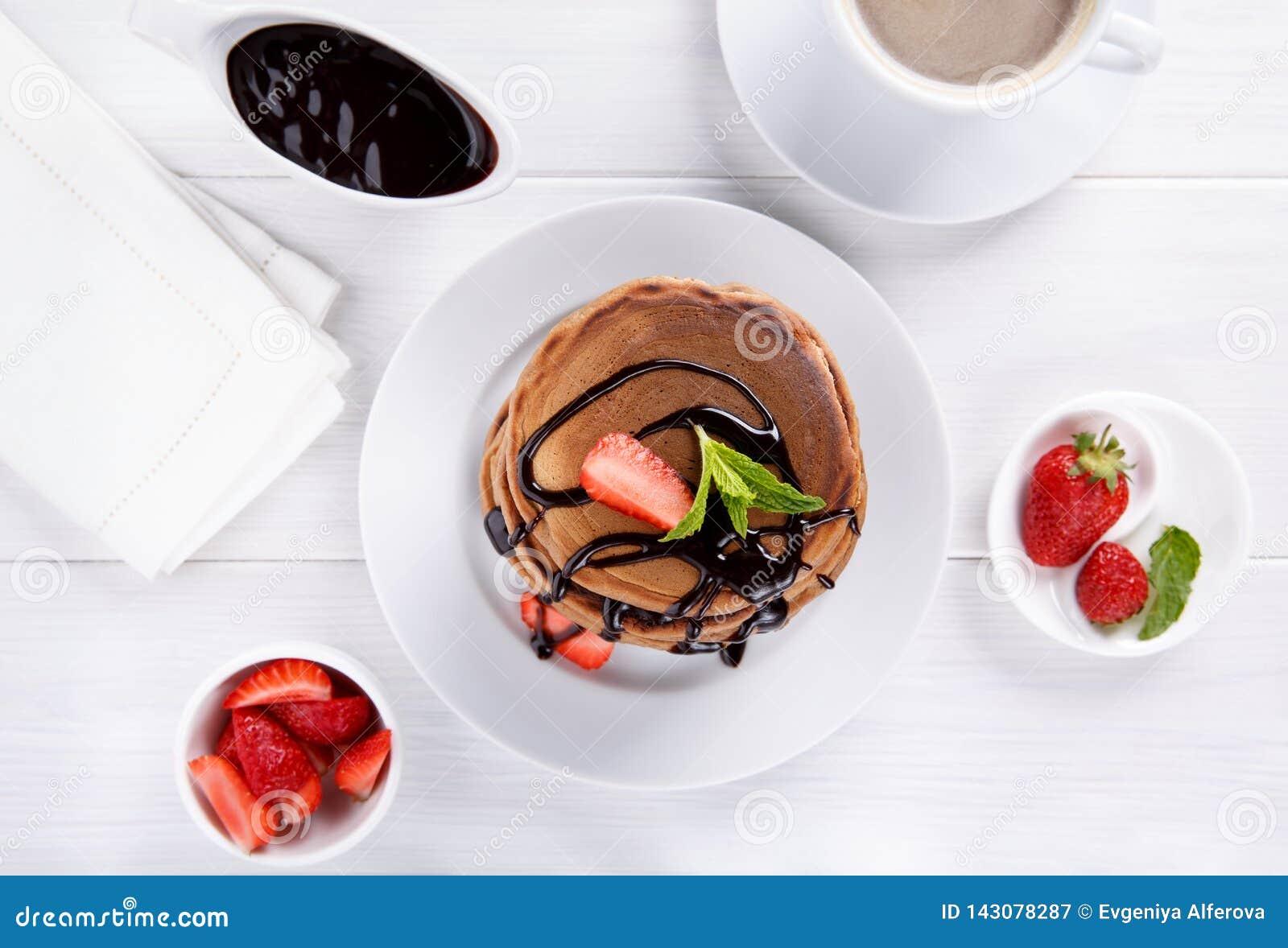 Pilha de panquecas do chocolate com cobertura e morangos do chocolate Vista superior