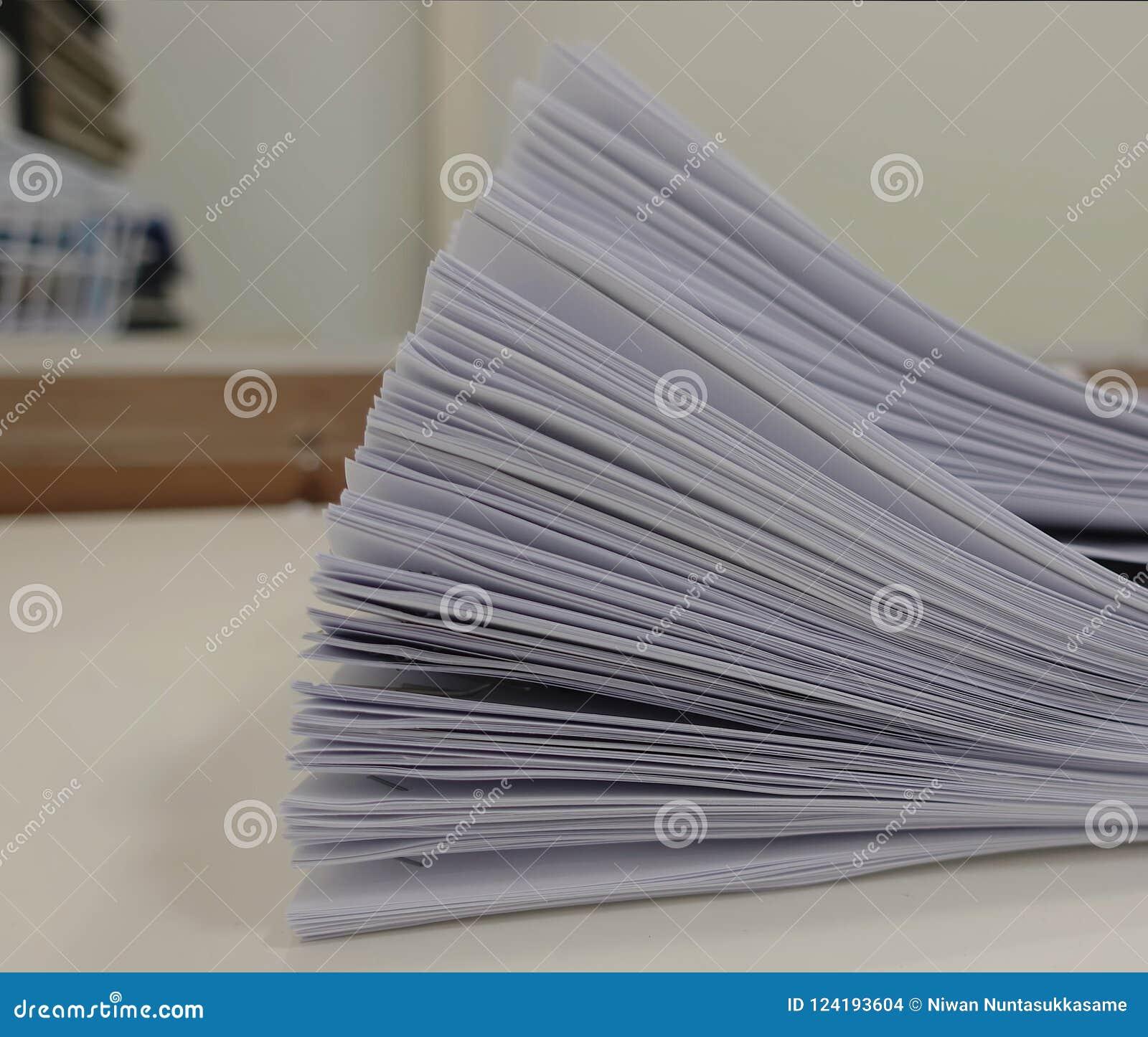 Pilha de papel de reunião na tabela com borrado da sala do escritório