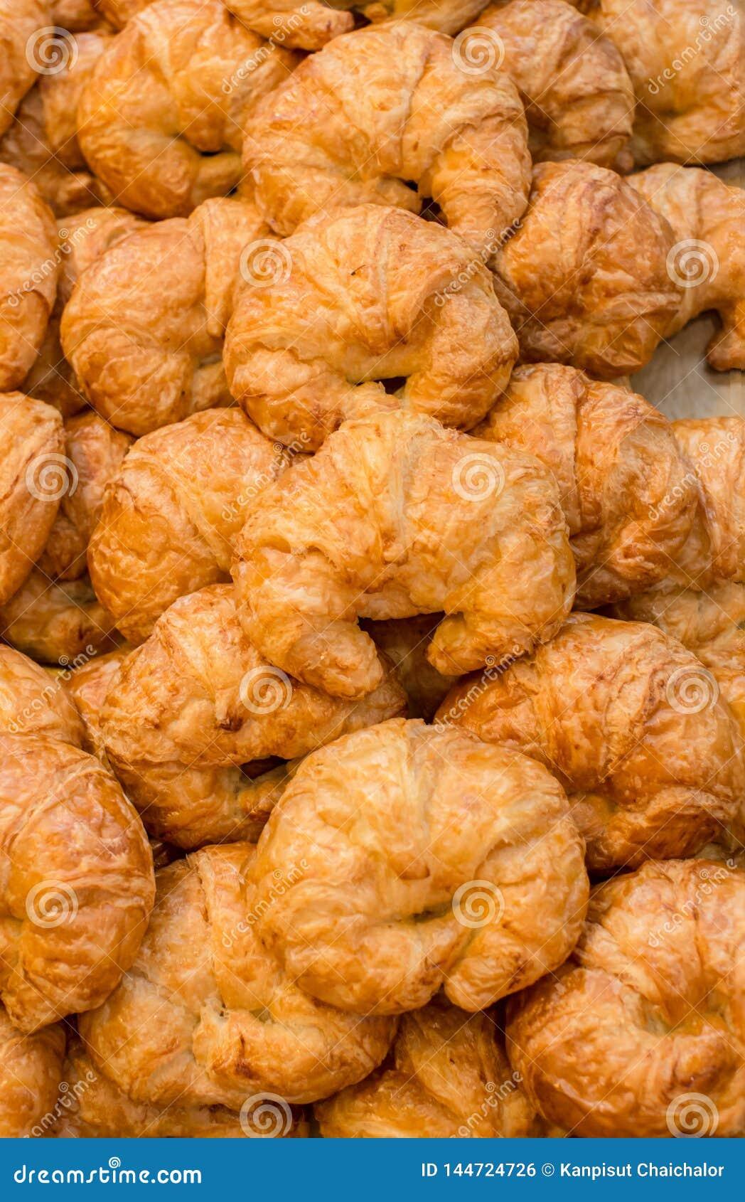 Pilha de pastelarias mouthwatering cozidas frescas do croissant da am?ndoa na cesta Croissants cozidos frescos Uma pilha do crois