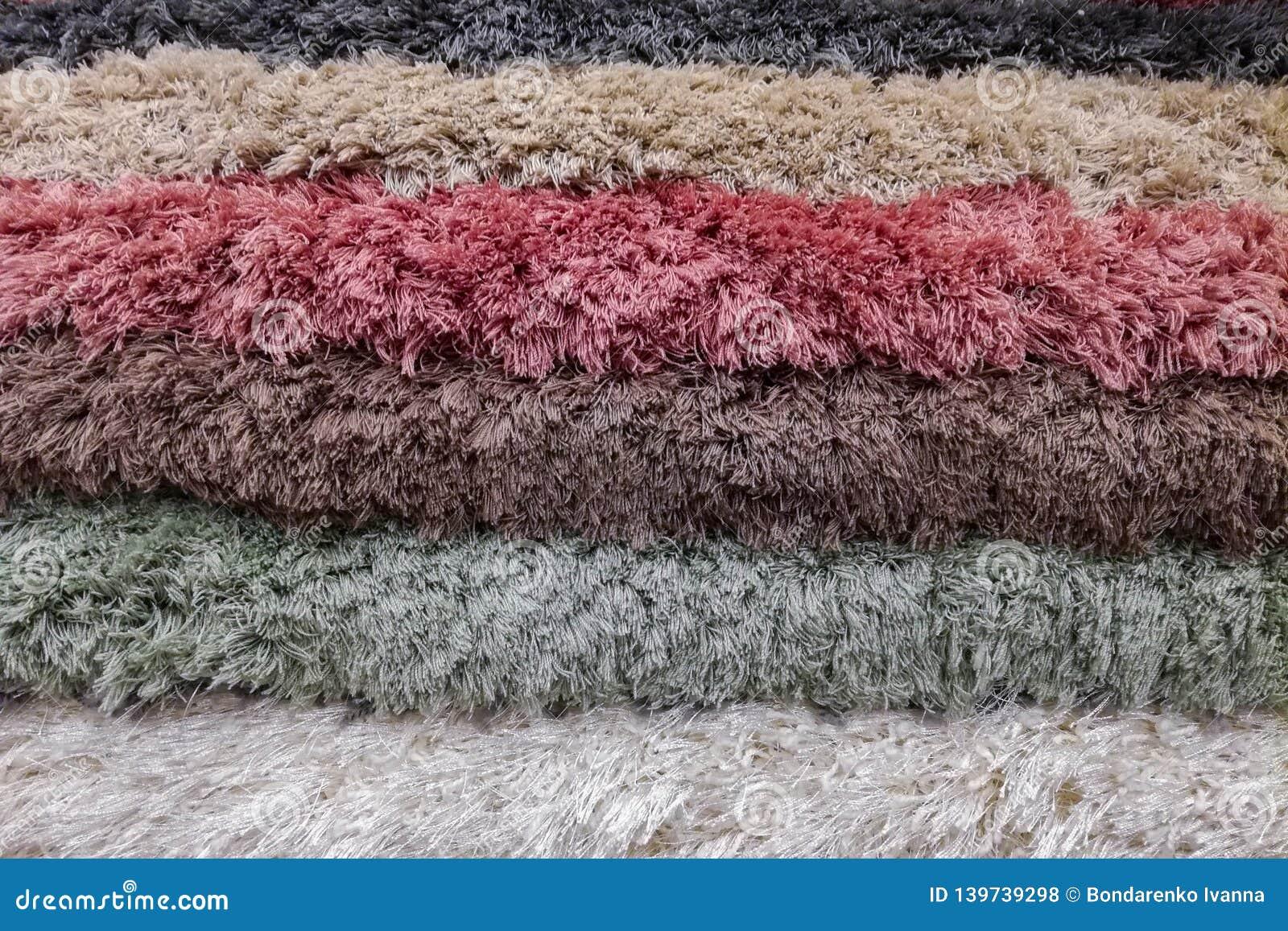 Pilha de tapetes ou de fundo colorido dos tapetes