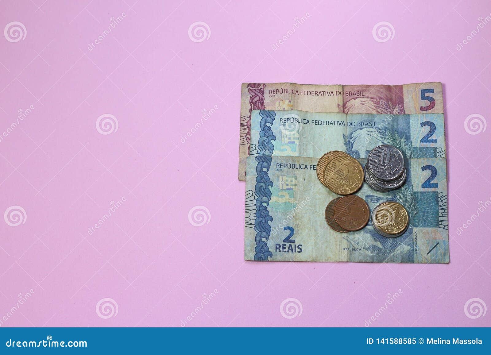 Pilha do baixo valor do dinheiro brasileiro no fundo cor-de-rosa com espaço da cópia para o texto