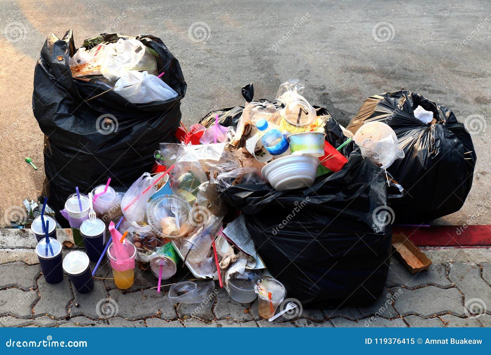 A pilha do preto plástico do lixo e o saco de lixo desperdiçam muitos no passeio, no lixo da poluição, no desperdício do plástico