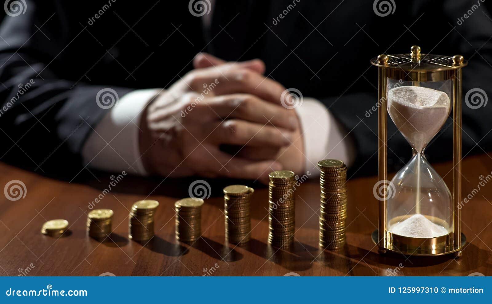 Pilhas do crescimento das moedas, areia que flui na ampulheta, lucro de espera do homem de negócios