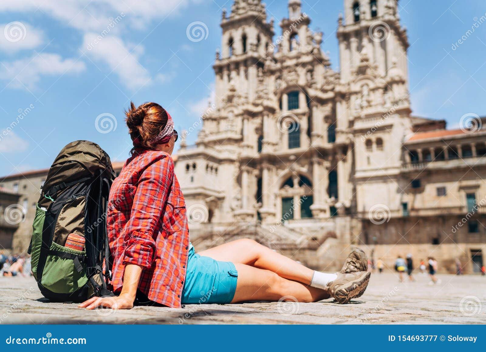 Piligrim fêmea novo do mochileiro que senta-se na plaza do quadrado de Obradeiro em Santiago de Compostela