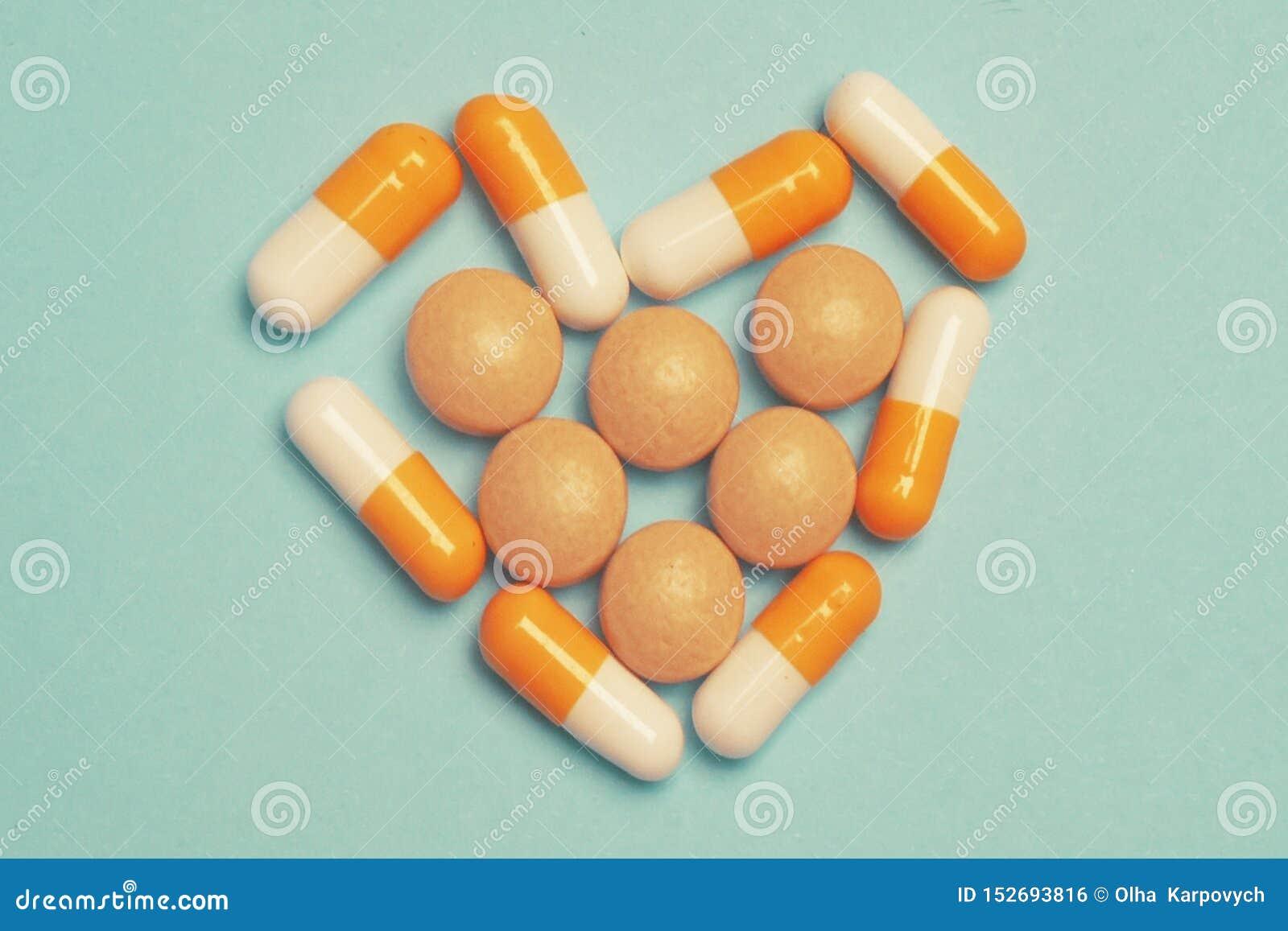 Pillen op een blauwe achtergrond Geassorteerde farmaceutische geneeskundepillen, tabletten en capsules, gezondheidsmacro Hartpill