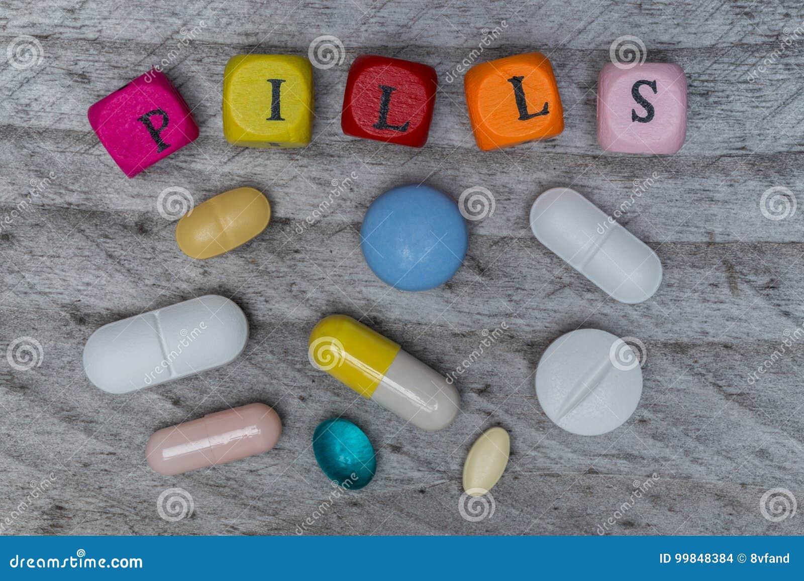 Pillenbuchstabewürfel und -tabletten auf grauem hölzernem Konzept