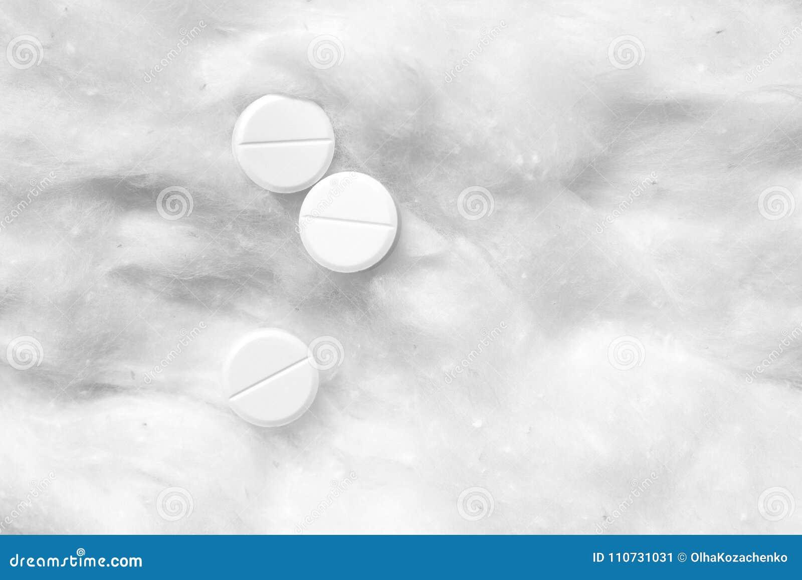Pillole bianche su ovatta medica Fondo astratto bianco
