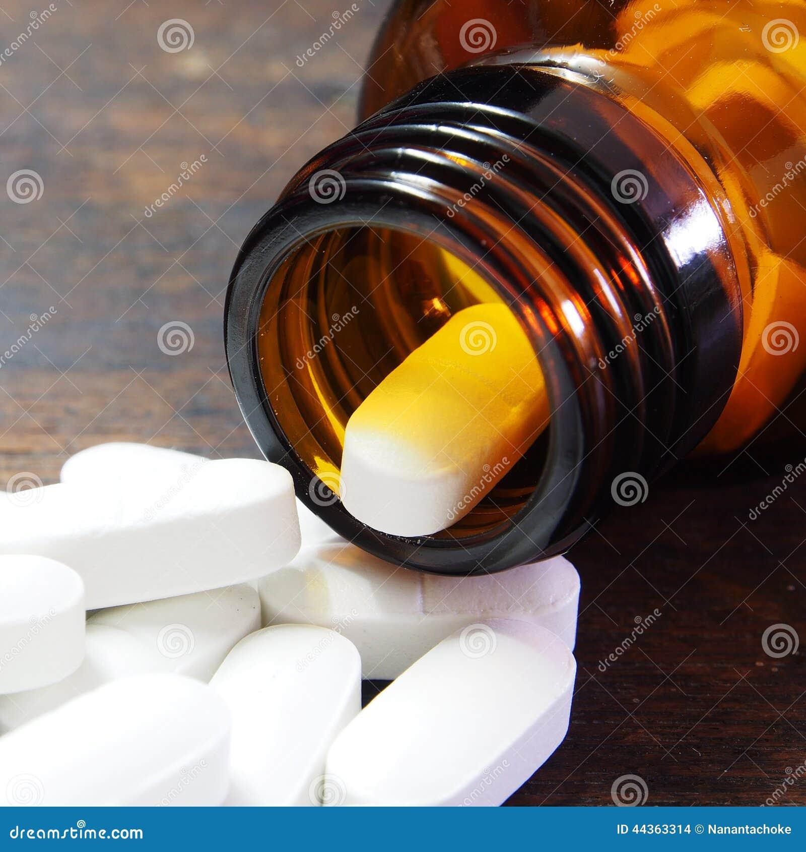 Pillole che si rovesciano da una bottiglia di pillola sulla tavola di legno
