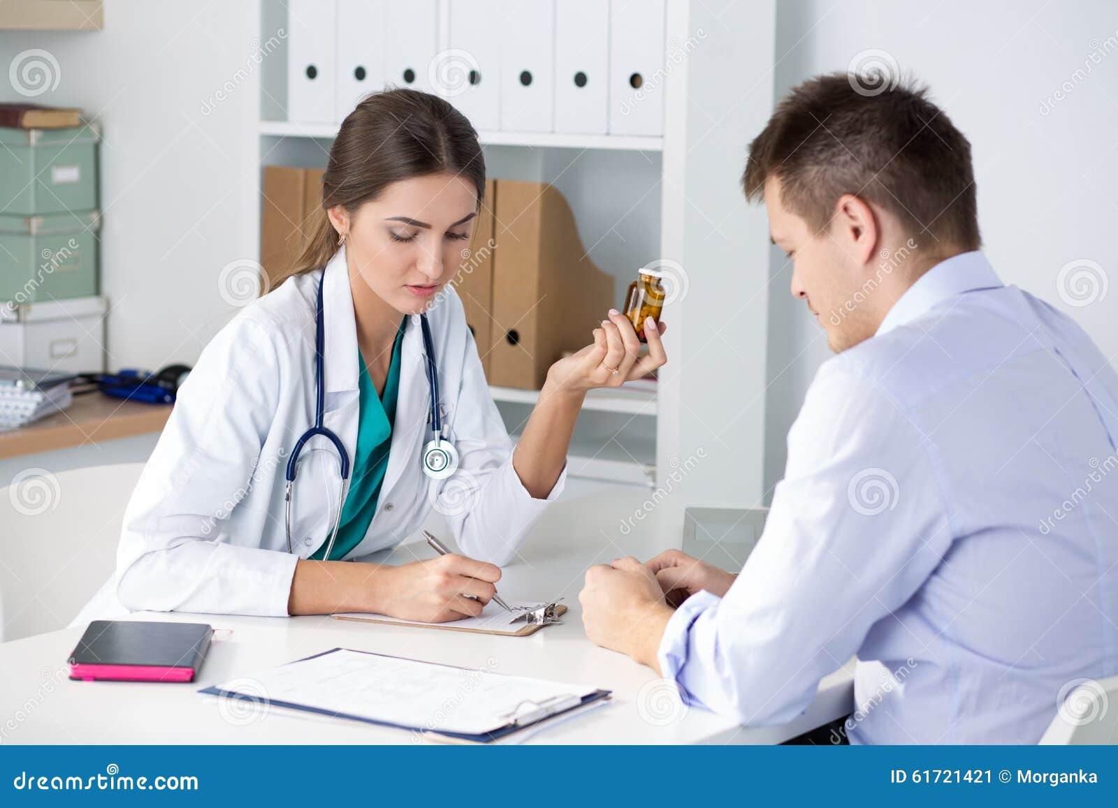 Pillole di prescrizione di medico femminile della medicina al suo paziente maschio