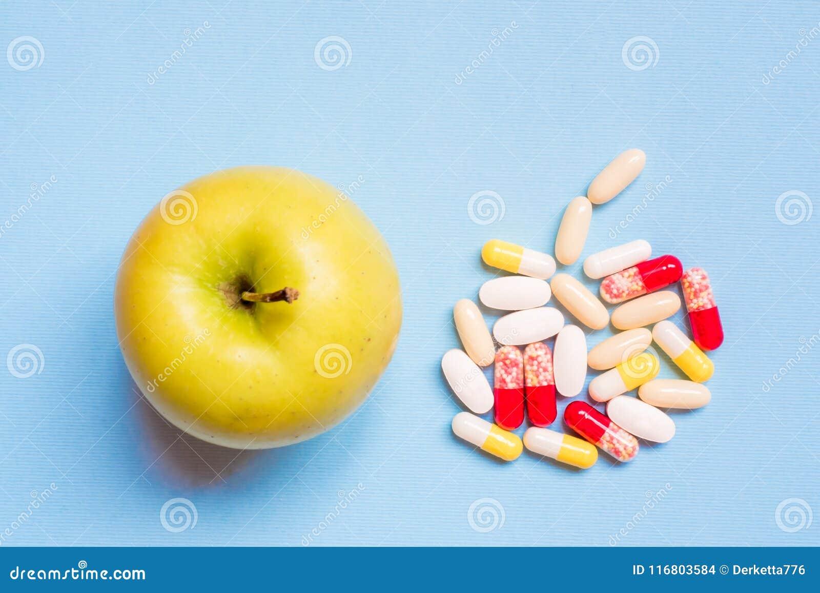 Pillole farmaceutiche differenti e Apple verde fresco su fondo blu