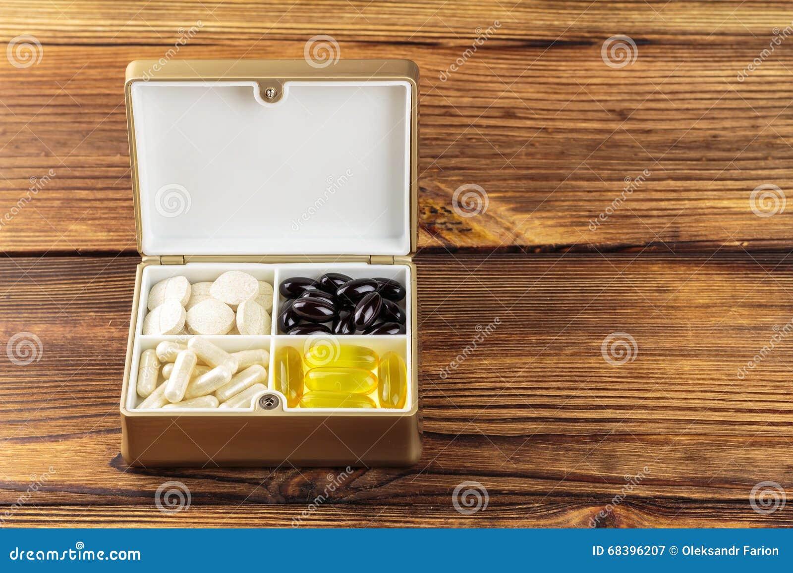 Pillole naturali miste dell integratore alimentare in contenitore, Omega 3, vitamina C, capsule del carotene su fondo di legno