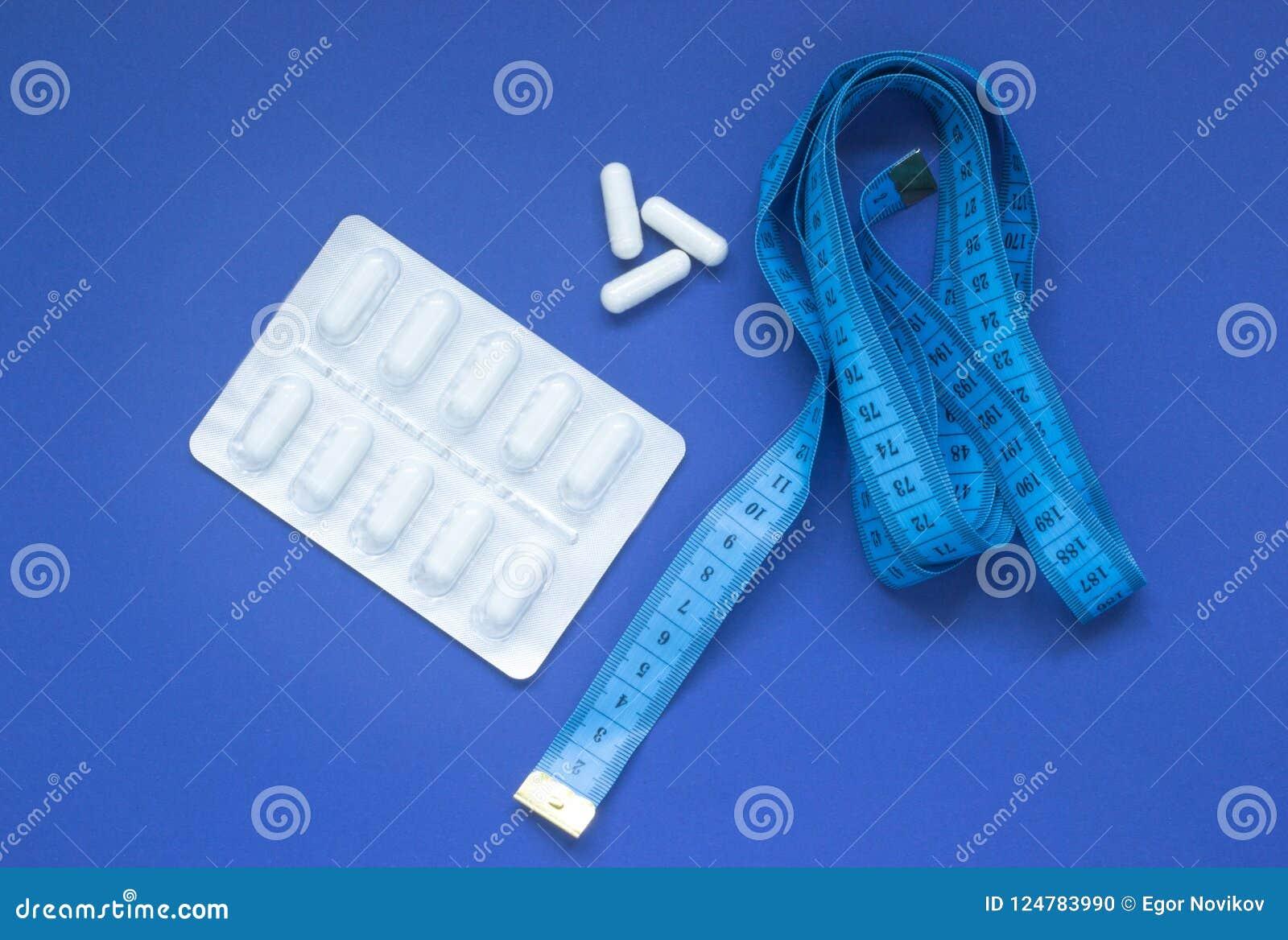 Pillole in una bolla ed in un nastro di misurazione su un fondo blu