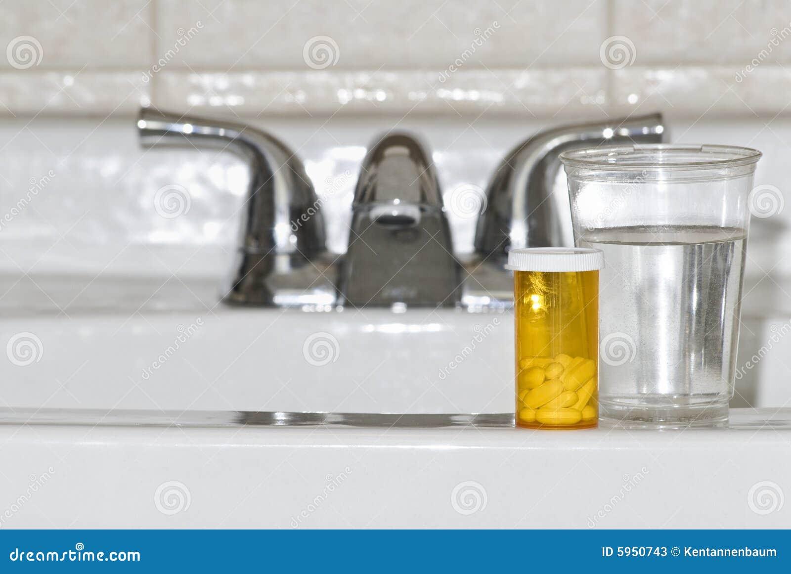 Pillules et eau sur le bassin de salle de bains