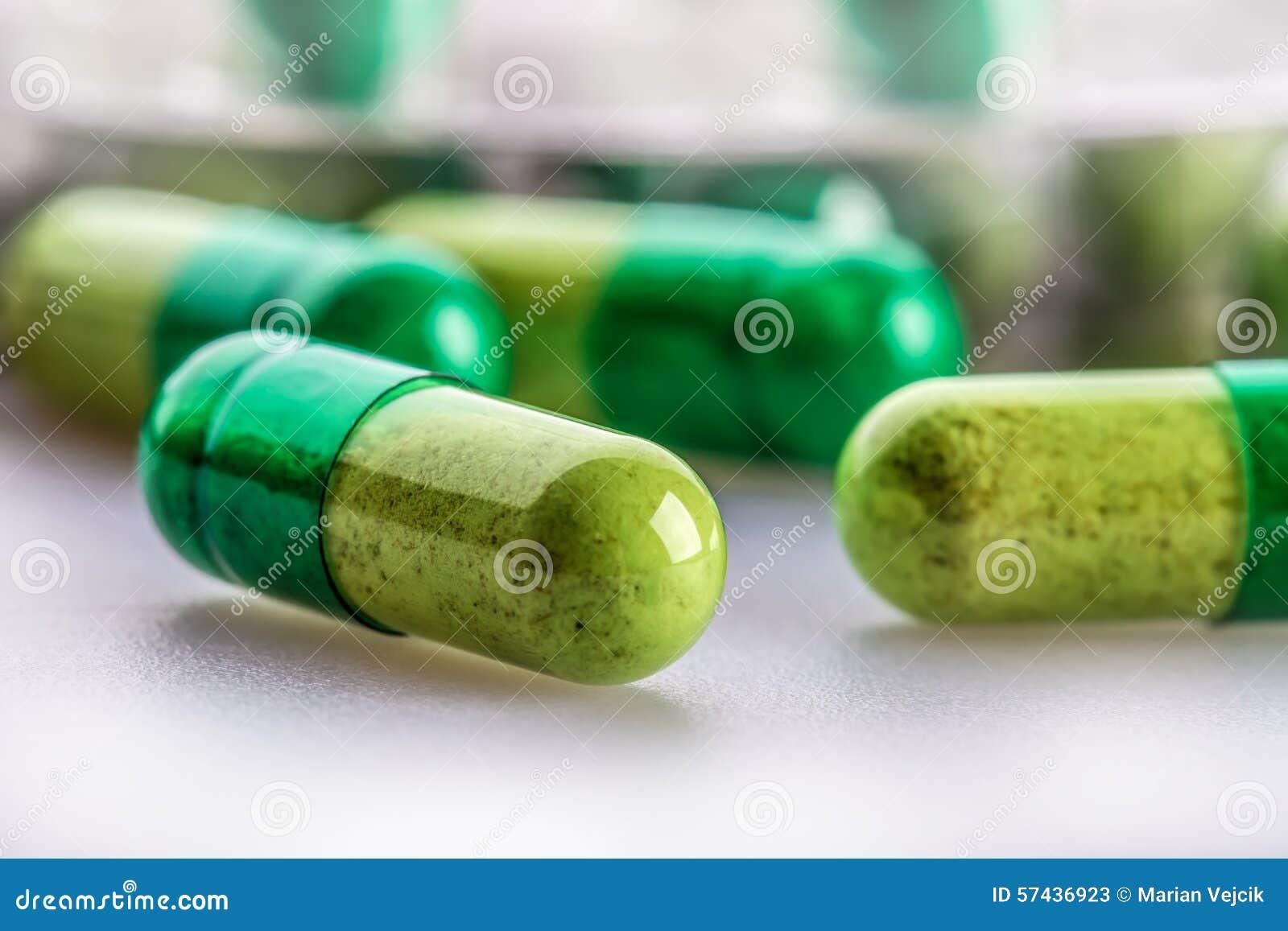 Pillules tablettes capsule Segment de mémoire des pillules Fond médical Plan rapproché de pile des comprimés de vert jaune