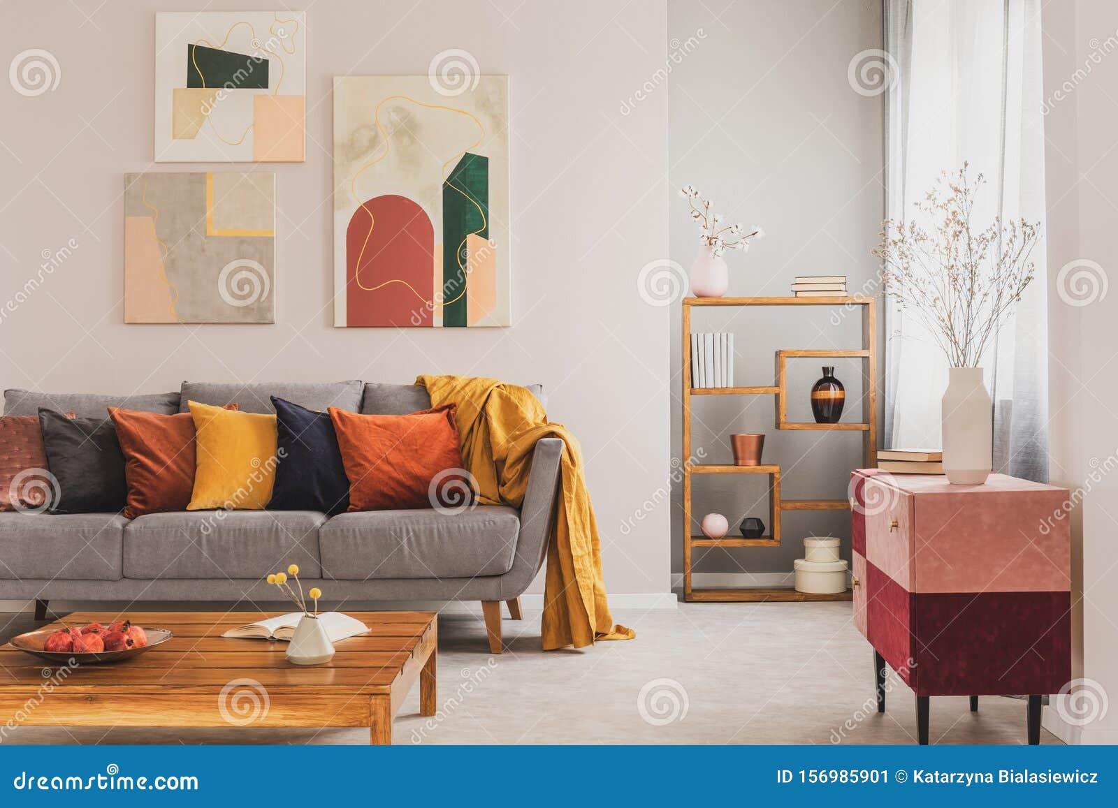 Cuscini Su Divano Marrone piloni gialli, arancioni, neri e marroni su un comodo divano