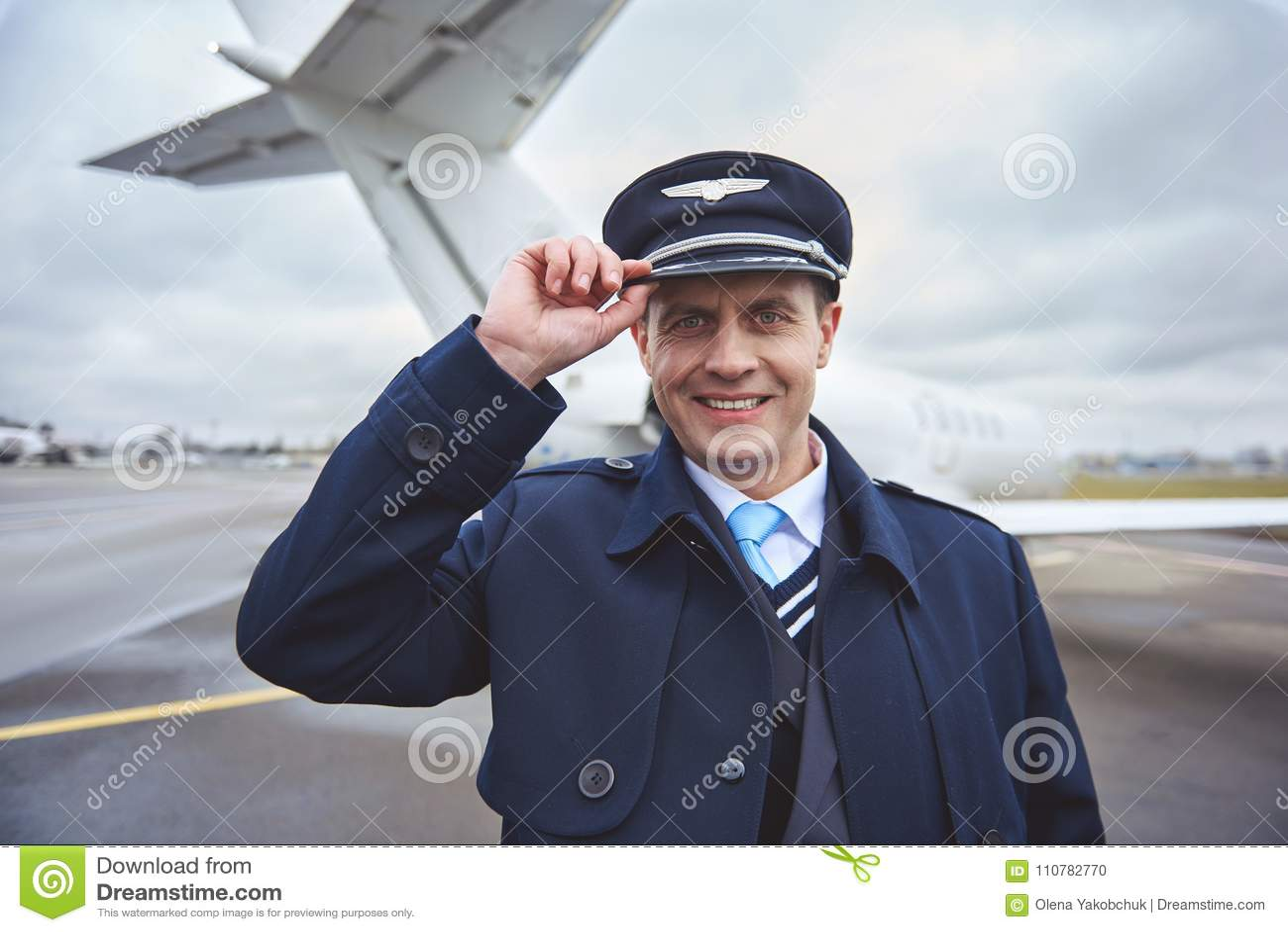 867ffcf498599 Retrato del aviador feliz que guarda el sombrero a mano mientras que mira la  cámara en la calle Concepto del empleo