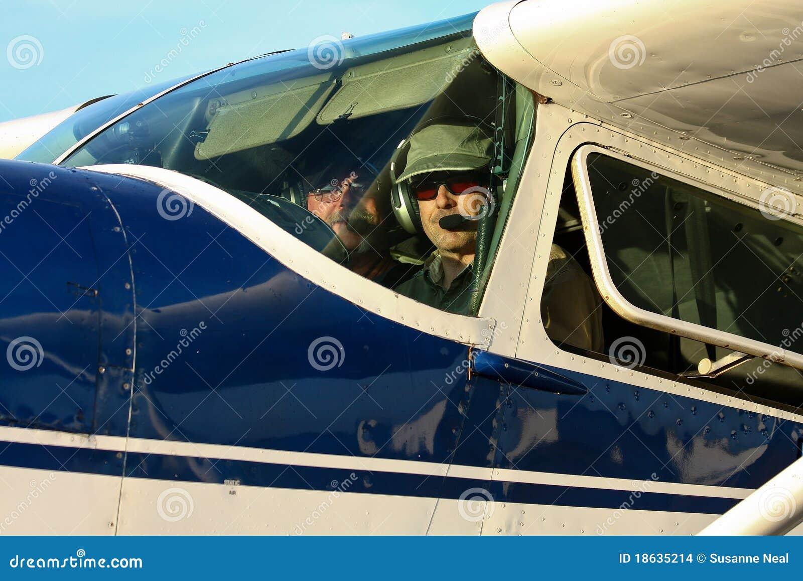 Piloto e copiloto na cabina do piloto de Cessna 180