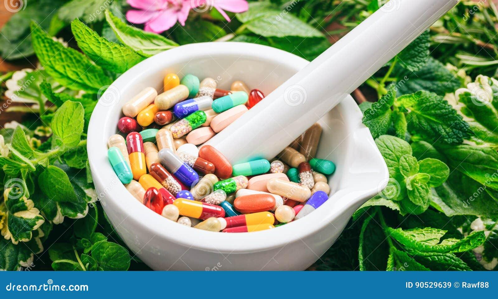 Pilules dans un mortier sur un fond frais d herbes