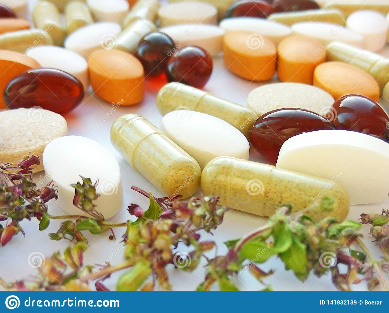 Pilules de phytothérapie avec les herbes naturelles sèches sur le fond blanc Concept de phytothérapie et de suppléments diététiqu