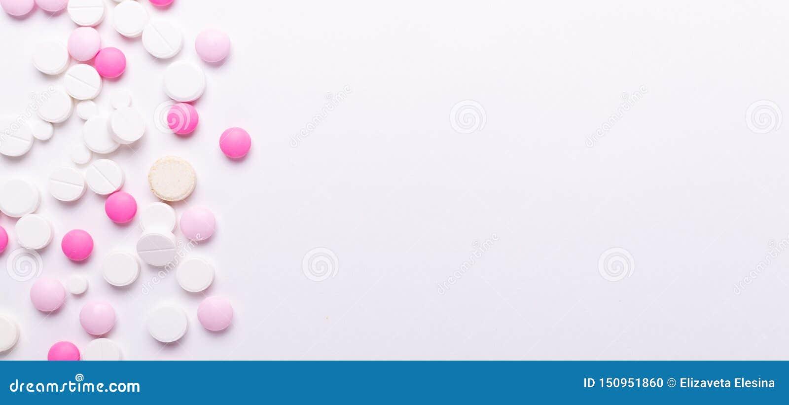 Pilules de rose et blanches sur le fond blanc Tas de divers comprimés et pilules assortis de médecine Banni?re horizontale