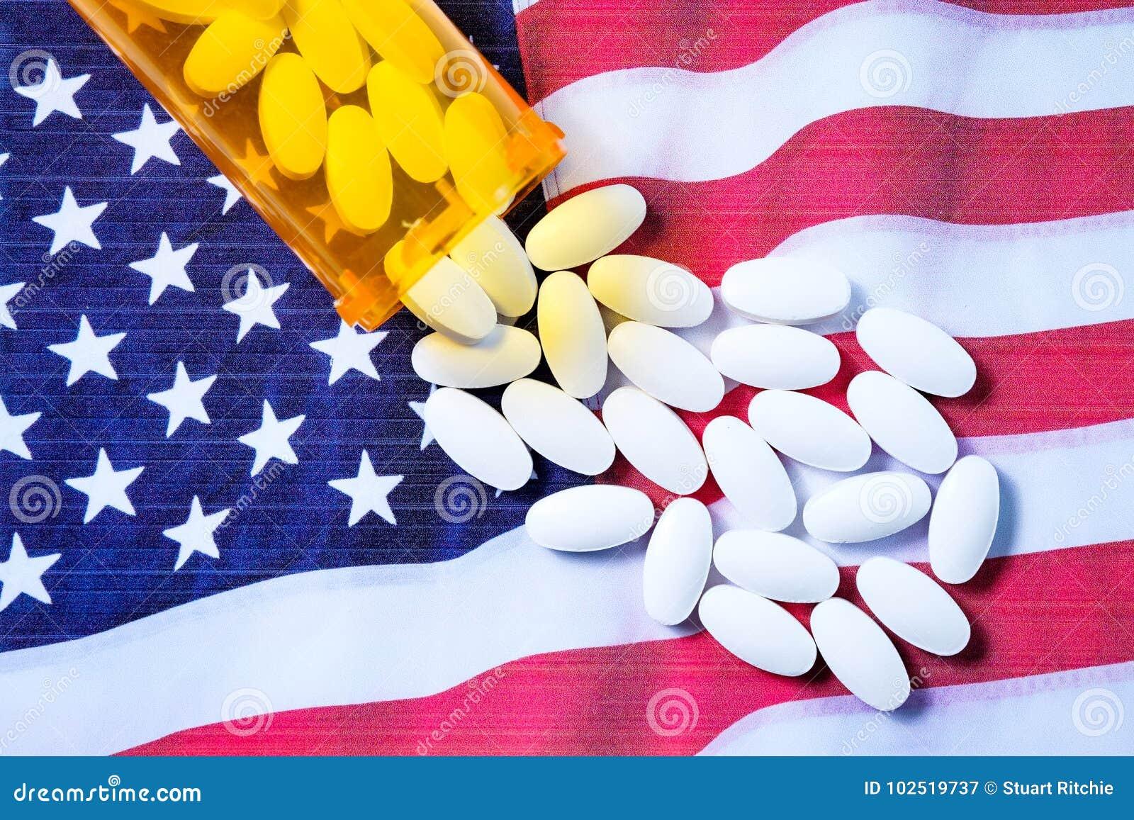 Pilules pharmaceutiques blanches débordant la bouteille de prescription au-dessus du drapeau américain