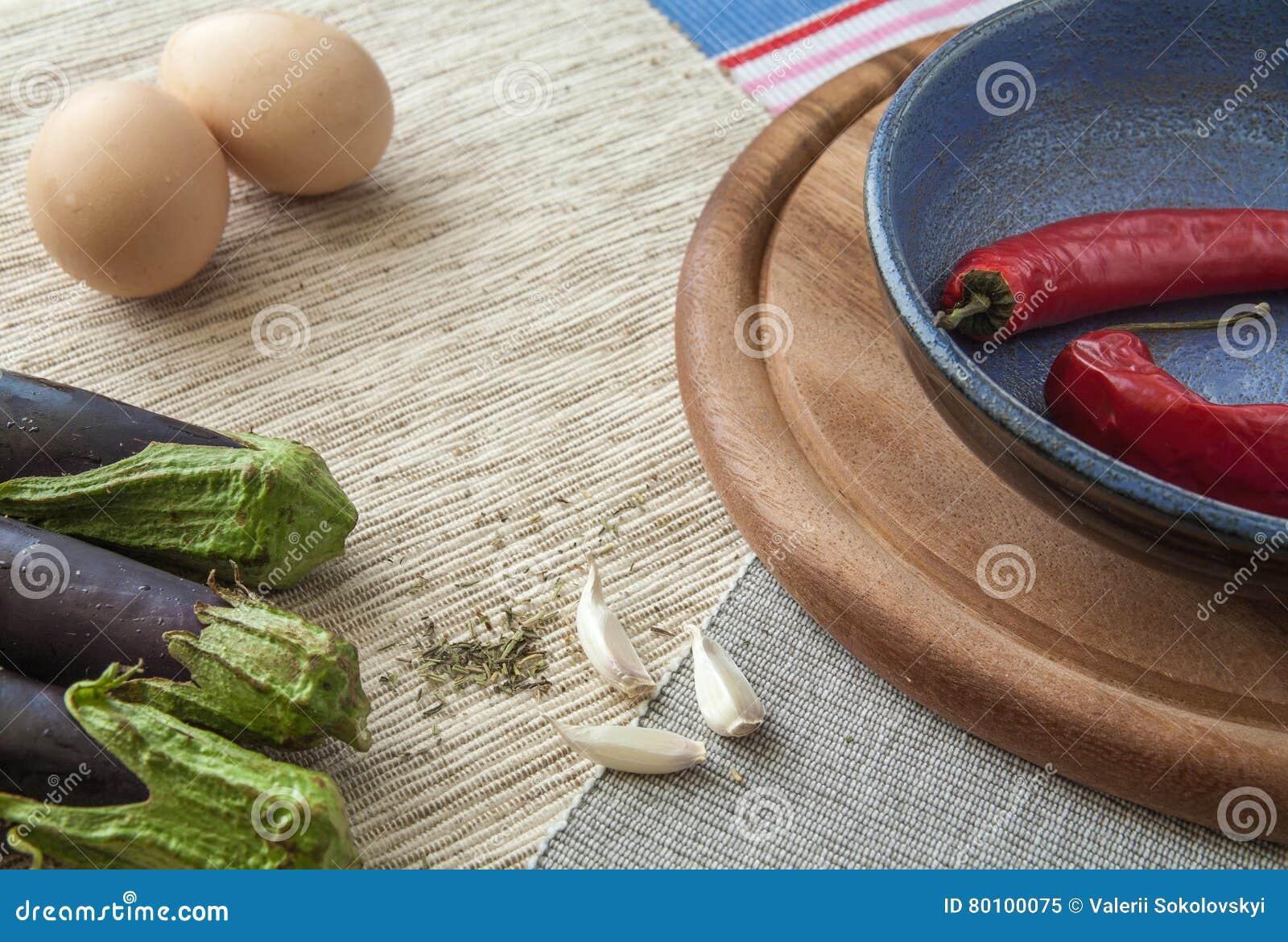 Pimentas de pimentão vermelho com ovos em uma tabela de madeira