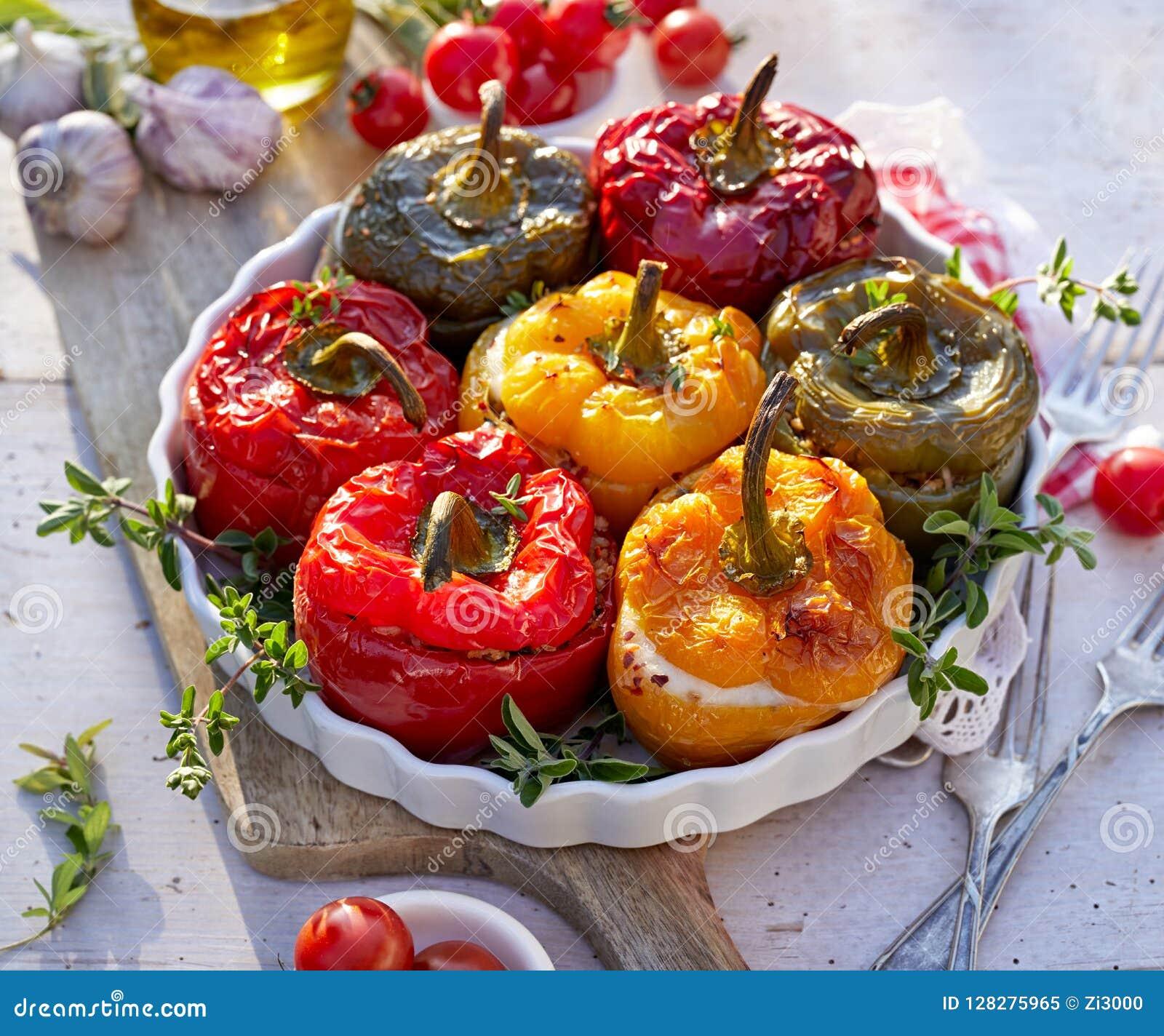 Pimentas de sino Roasted com o cogumelo, o arroz, o queijo e as ervas enchendo-se em um prato do cozimento em uma tabela de madei