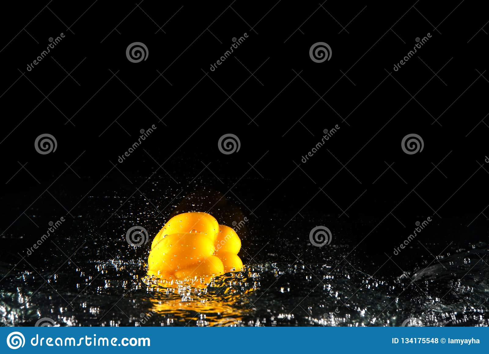 Pimento de Bell amarela fresco com respingo e bolha da água Copie o espaço Paprika Dropped amarela suculenta na água no preto