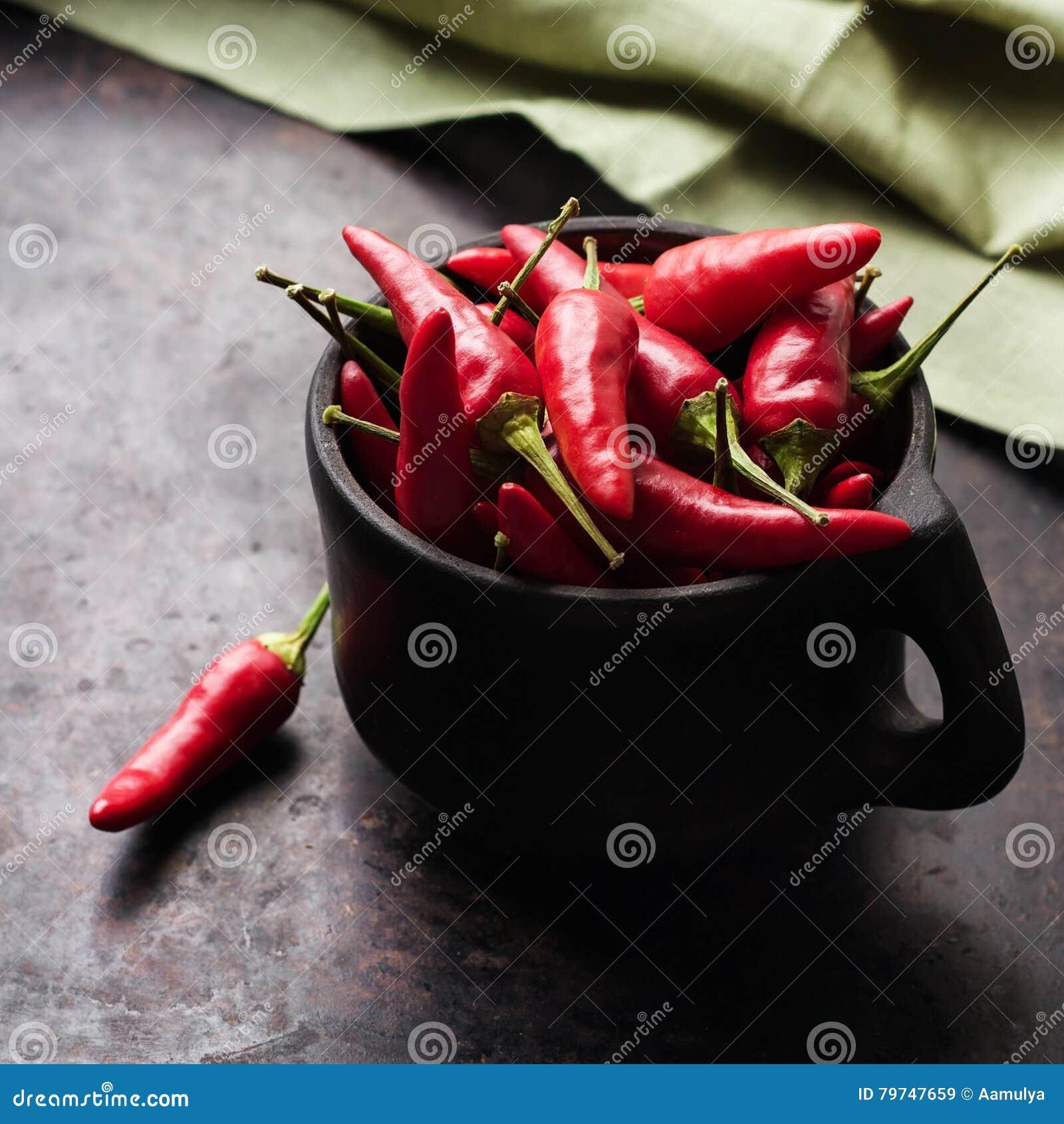 Pimientas de chile rojo crudas en una tabla oxidada negra