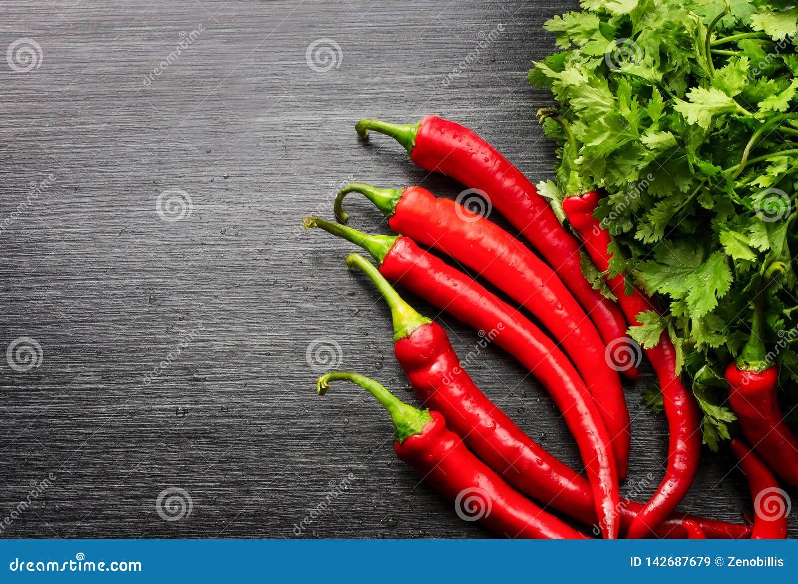 Pimiento rojo de las pimientas de cayena annuum y verdor en la tabla de madera Visi?n superior