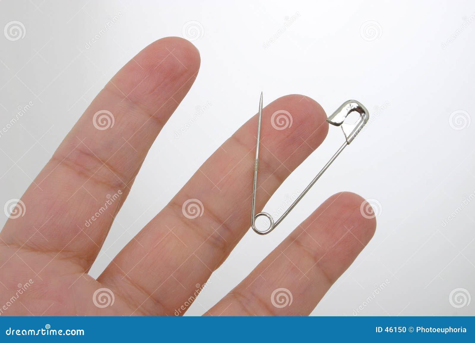 Pin de seguridad pegado en dedo