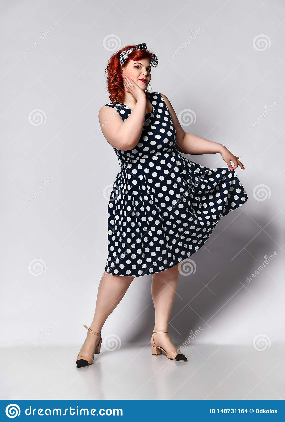 Pin up a female portrait. Beautiful retro fat woman in polka dot dress with red lips and manicure nails and old-style haircut