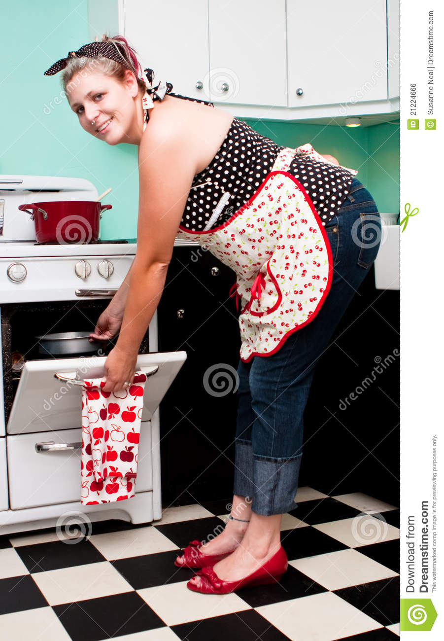 293b3adb5ea A modern pinup girl is bending over and putting a cake pan in her retro  oven. She is wearing folded up jeans