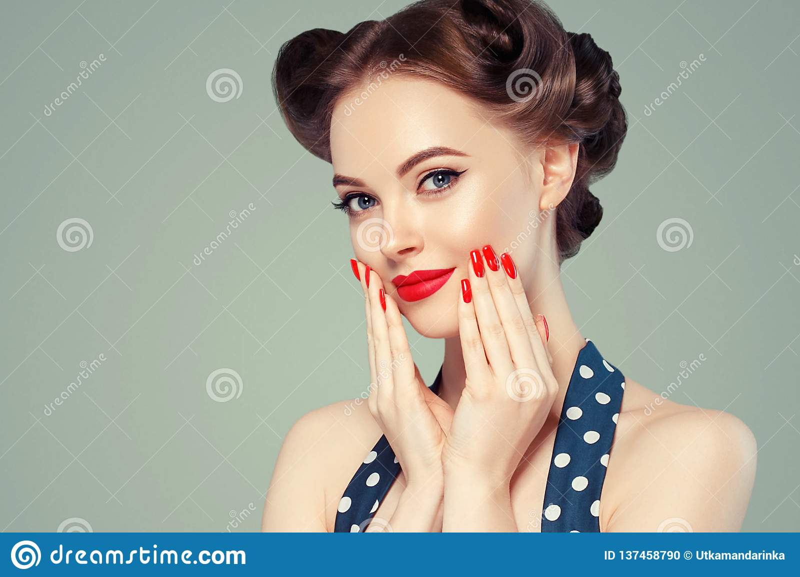 Pin up girl vintage. Beautiful woman pinup style portrait in retro dress and makeup, manicure nails hands, red lipstick and polka