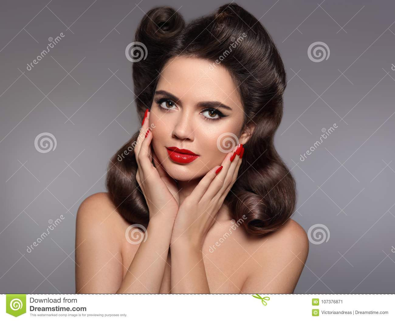 Pin up hairstyle. Beautiful 50s girl holding her cheeks with red