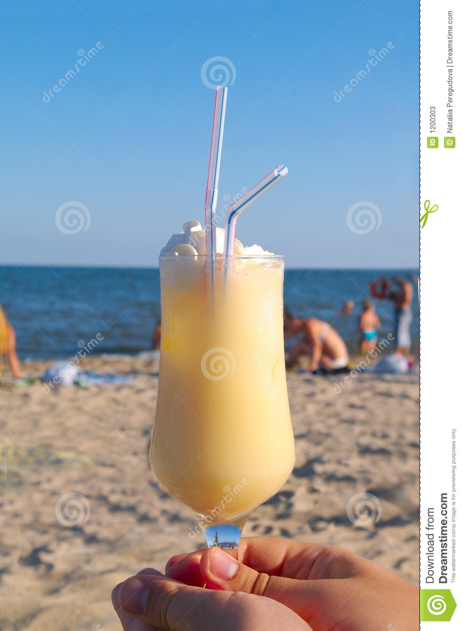 Pina-colada cocktail on the beach in woman hand